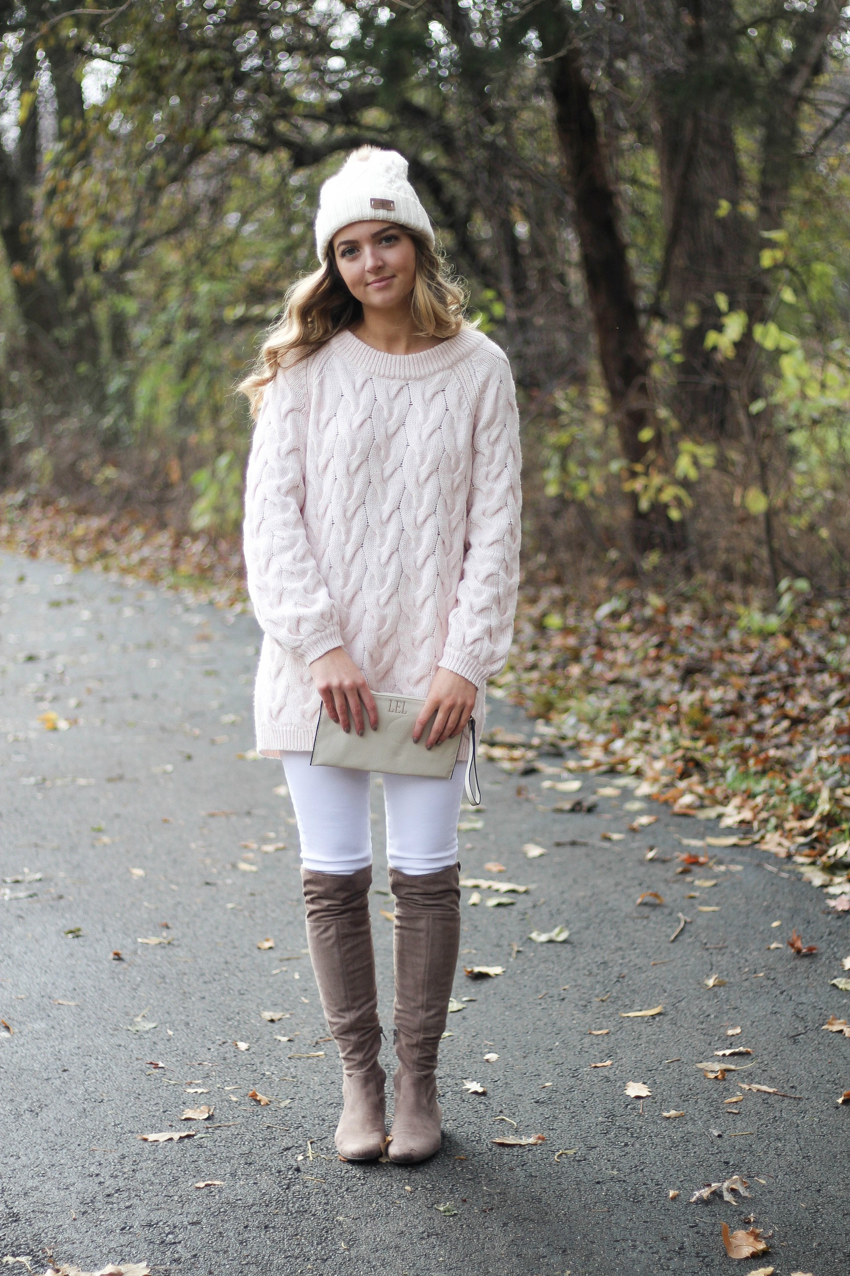 Pink cable knit sweater with white jeans and over the knee tan suede boots topped with an adorable faux fur beanie! The perfect winter outfit by Lauren Lindmark on dailydoseofcharm.com daily dose of charm