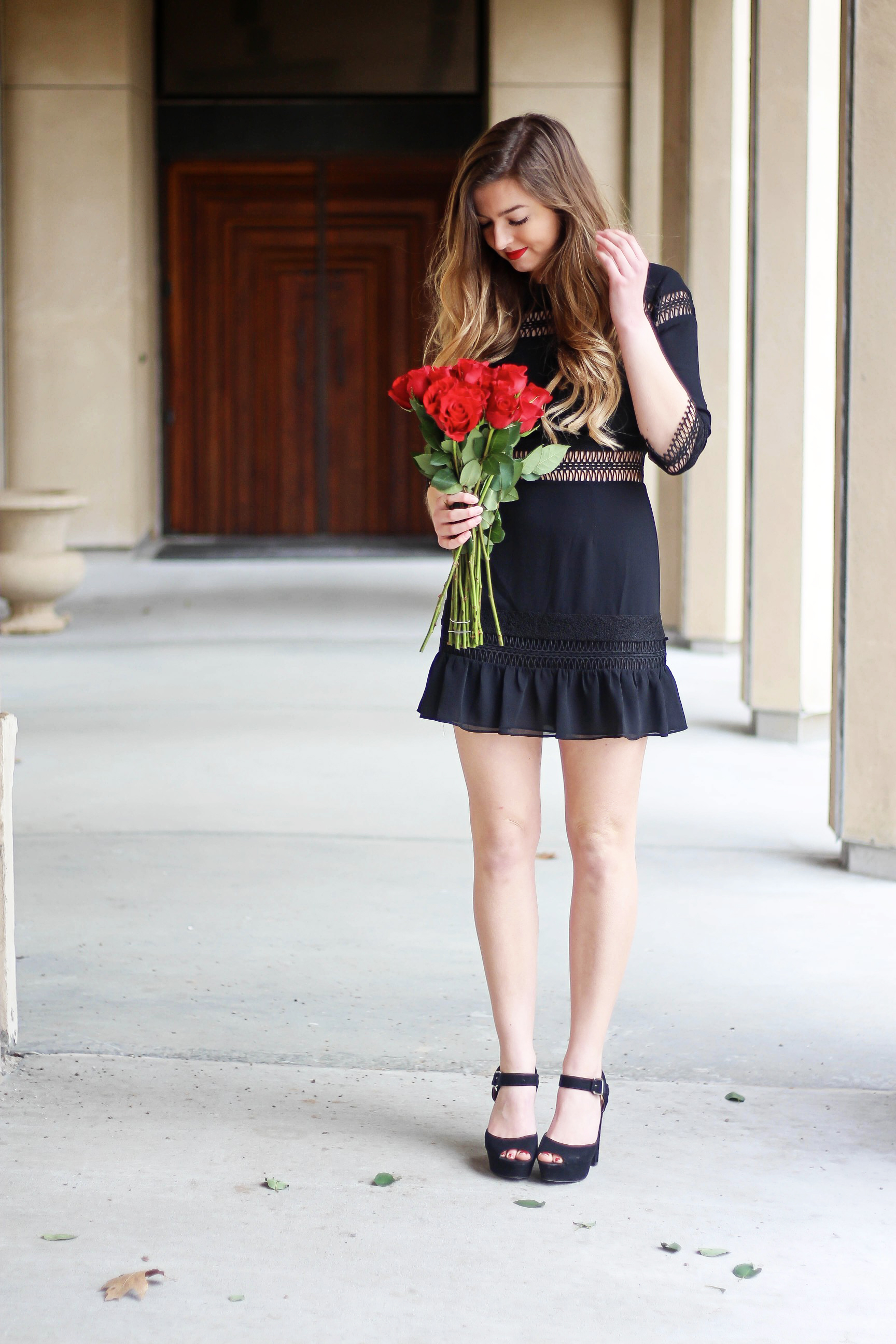 Valentines Day outfit! This little black dress is so perfect for any special occasion. I love the lace details around the waste and on the sleeves! I paired it with some chunky black heels, cluster earrings, and red lips! Plus of course some roses! By Lauren Lindmark on daily dose of charm dailydoseofcharm.com
