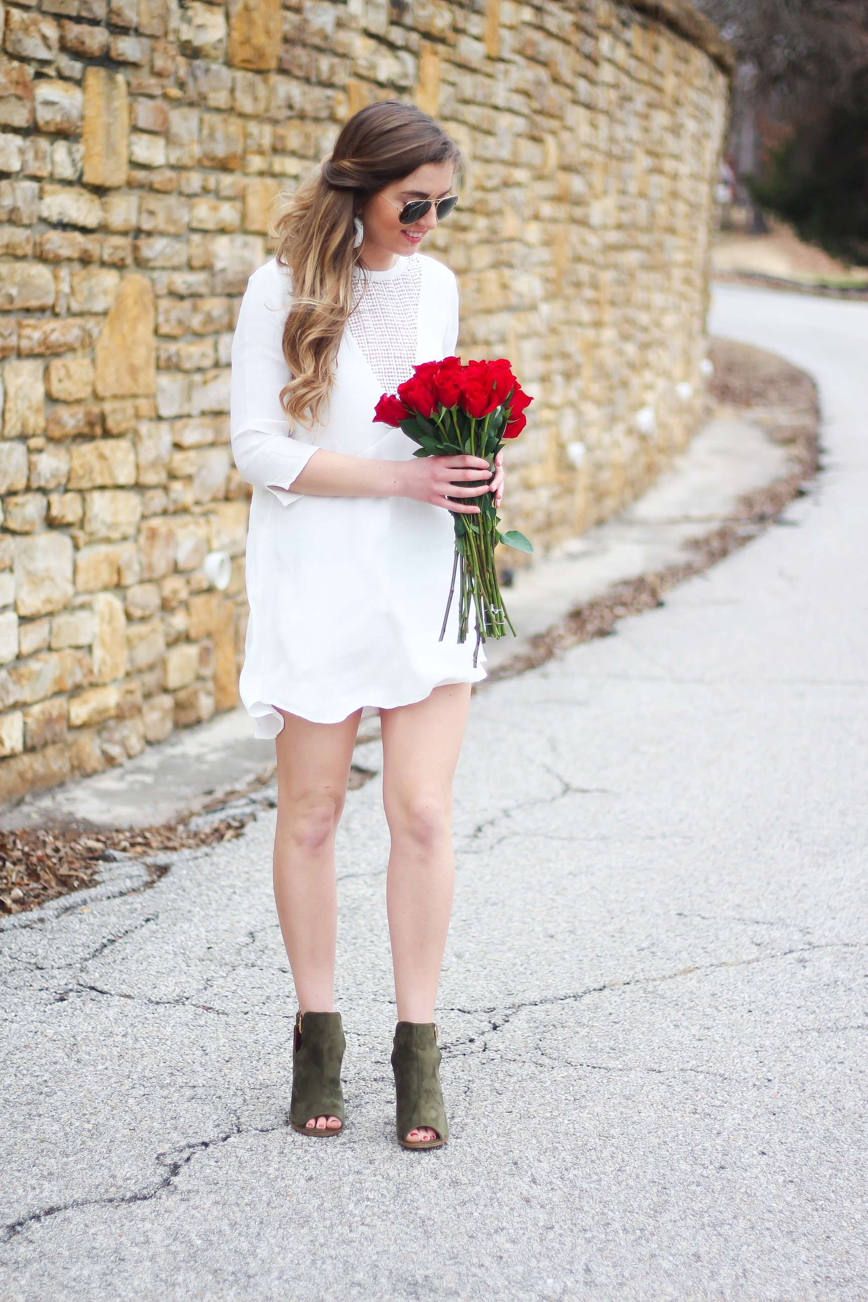 Perfect Valentine's Day look! If you need to know what to wear for Valentines Day look no further! Love this white deep vneck lace dress, especially with hunter green booties! I paired it with white Kendra Scott earrings and my ray ban aviators! By Lauren Lindmark daily dose of charm on dailydoseofcharm.com