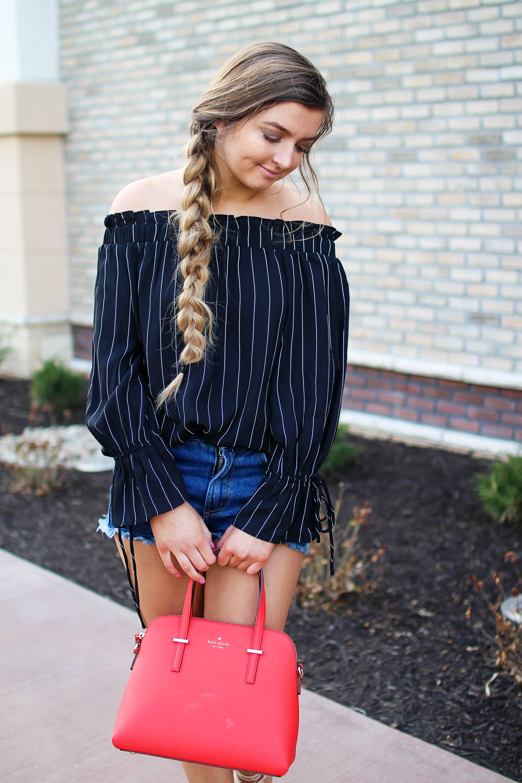 The cutest black striped off the shoulder top paired with jean shorts and a red Kate Spade purse. My favorite tassel shoes go perfectly with this look! I finished off the look with my long hair in a side braid. I love this outfit idea! By Lauren Lindmark on daily dose of charm dailydoseofcharm.com