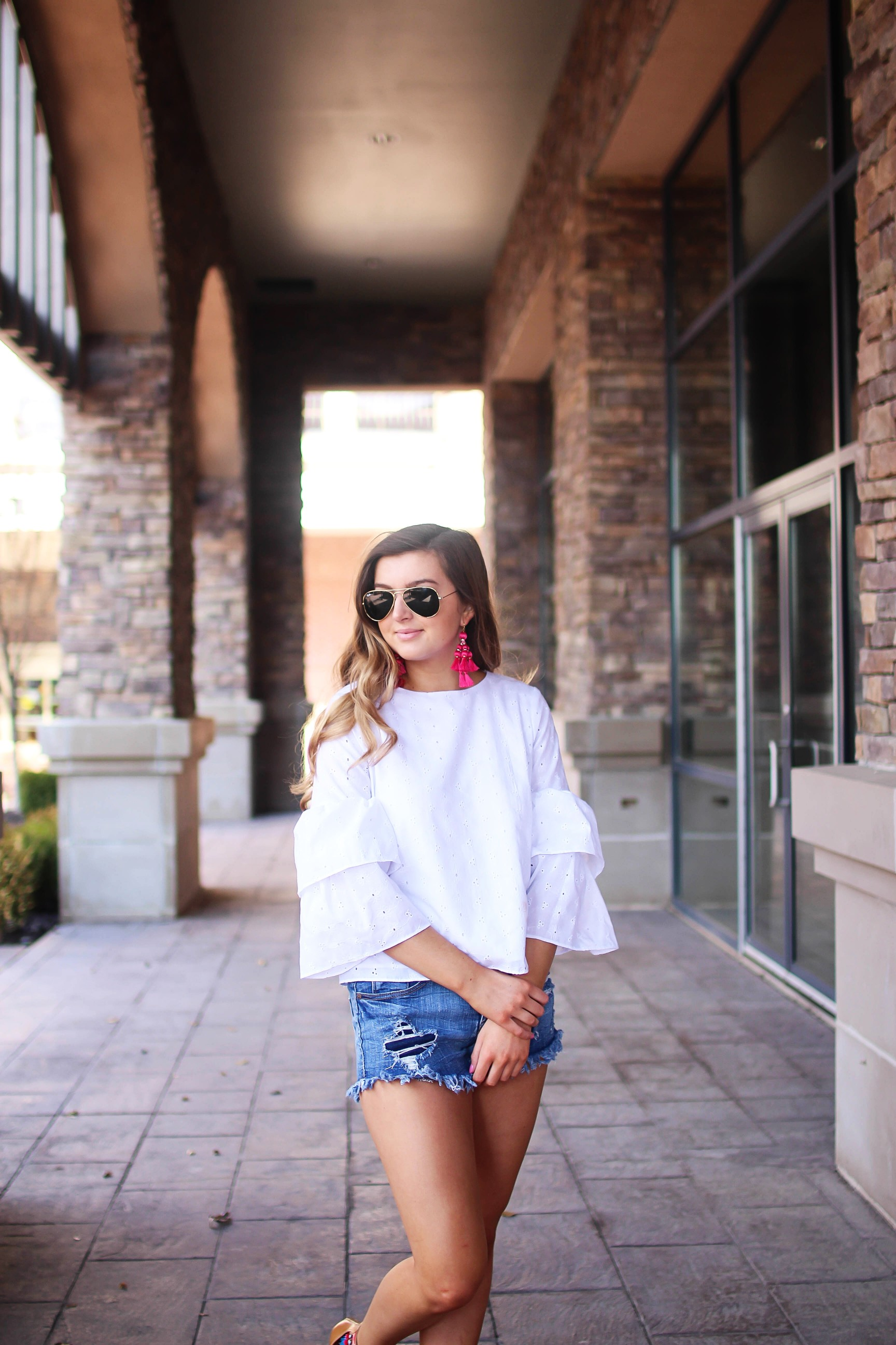 The cutest fiesta top ever! The ruffle sleeves on the top are so unique and such a cute outfit idea! I paired it with ripped jeans shorts and my tassel sandals and Kate Spade tassel earrings! By Lauren Lindmark on dailydoseofcharm.com daily dose of charm