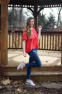 Free people flowy top in a pretty coral color paired with ripped jeans and white and gold New Balance sneakers! I love these gold sneakers so much! By Lauren Lindmark on daily dose of charm dailydoseofcharm.com