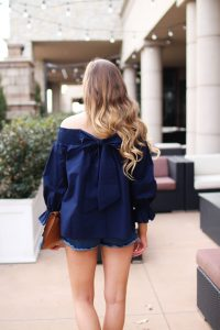 The cutest and most unique off the shoulder top you'll ever find! I love the bow on the back of the off the shoulder top and the unique sleeves. I paired it with the cutest tassel clutch and Tory Burch sandals! By Lauren Lindmark on daily dose of charm dailydoseofcharm.com