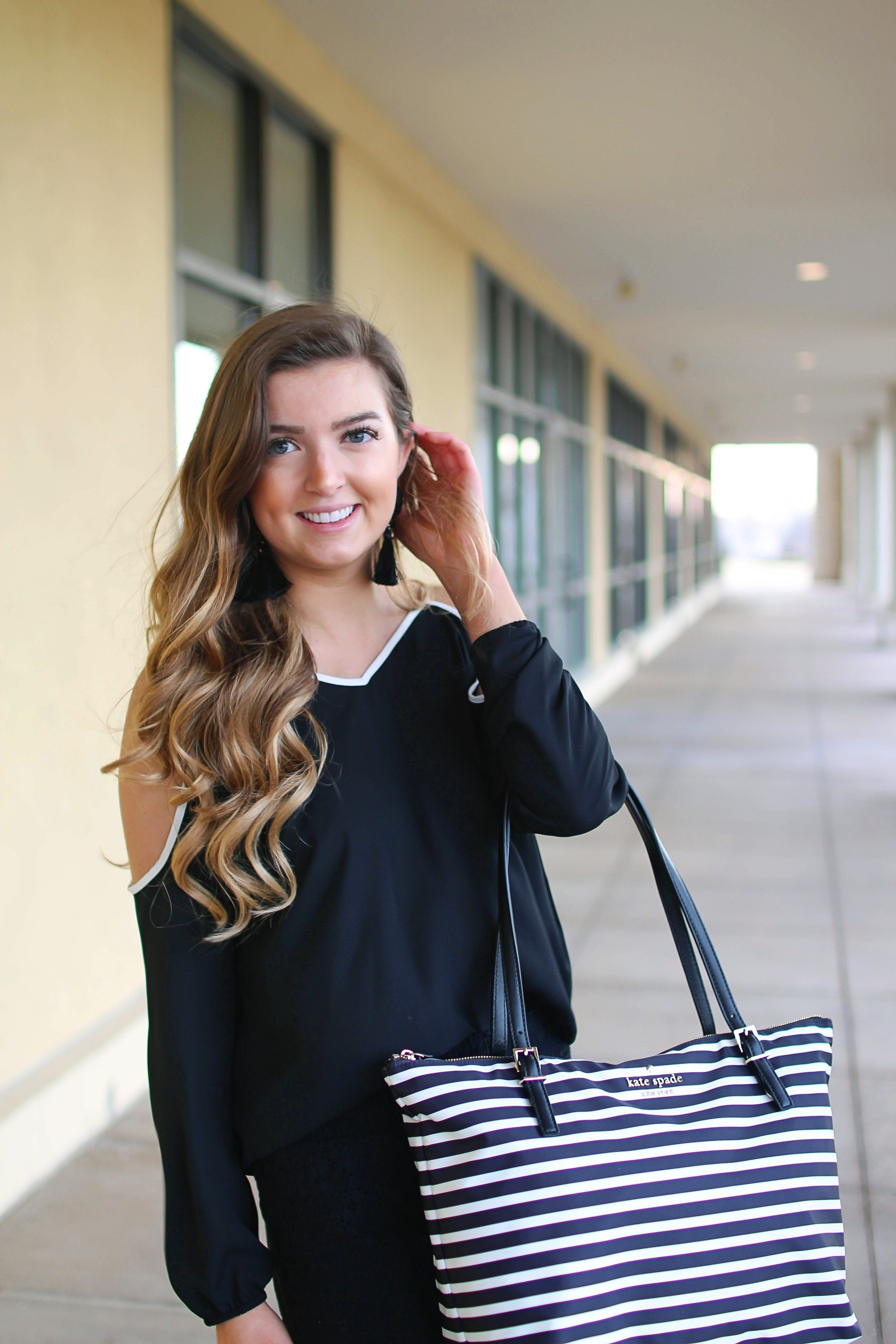 Black and white outfit! I love this black cold shoulder top with the white trim detail! I paired ti with some comfy black cotton shorts and my new black and white striped Kate spade tote! To finish off the outfit I put on my tassel earrings that are only $12! By Lauren Lindmark on Daily Dose of Charm dailydoseofcharm.com