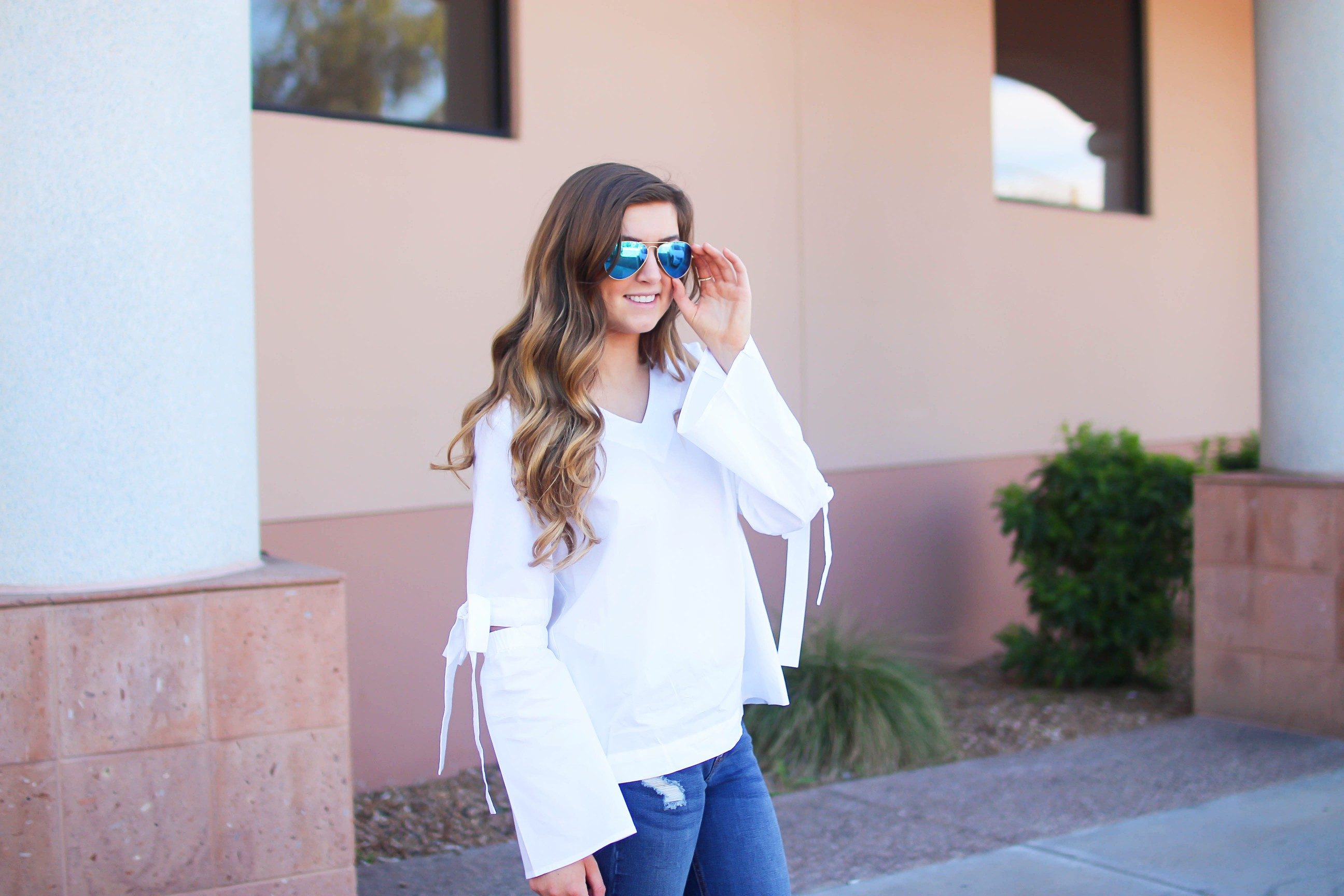 Love this white bow sleeve top that's only $28! It's so cute and classy, plus can be worn with so many things! I paired this top with my favorite ripped jeans, tory burch miller, and blue mirrored ray ban aviators! By Lauren Lindmark on dailydoseofcharm.com daily dose of charm