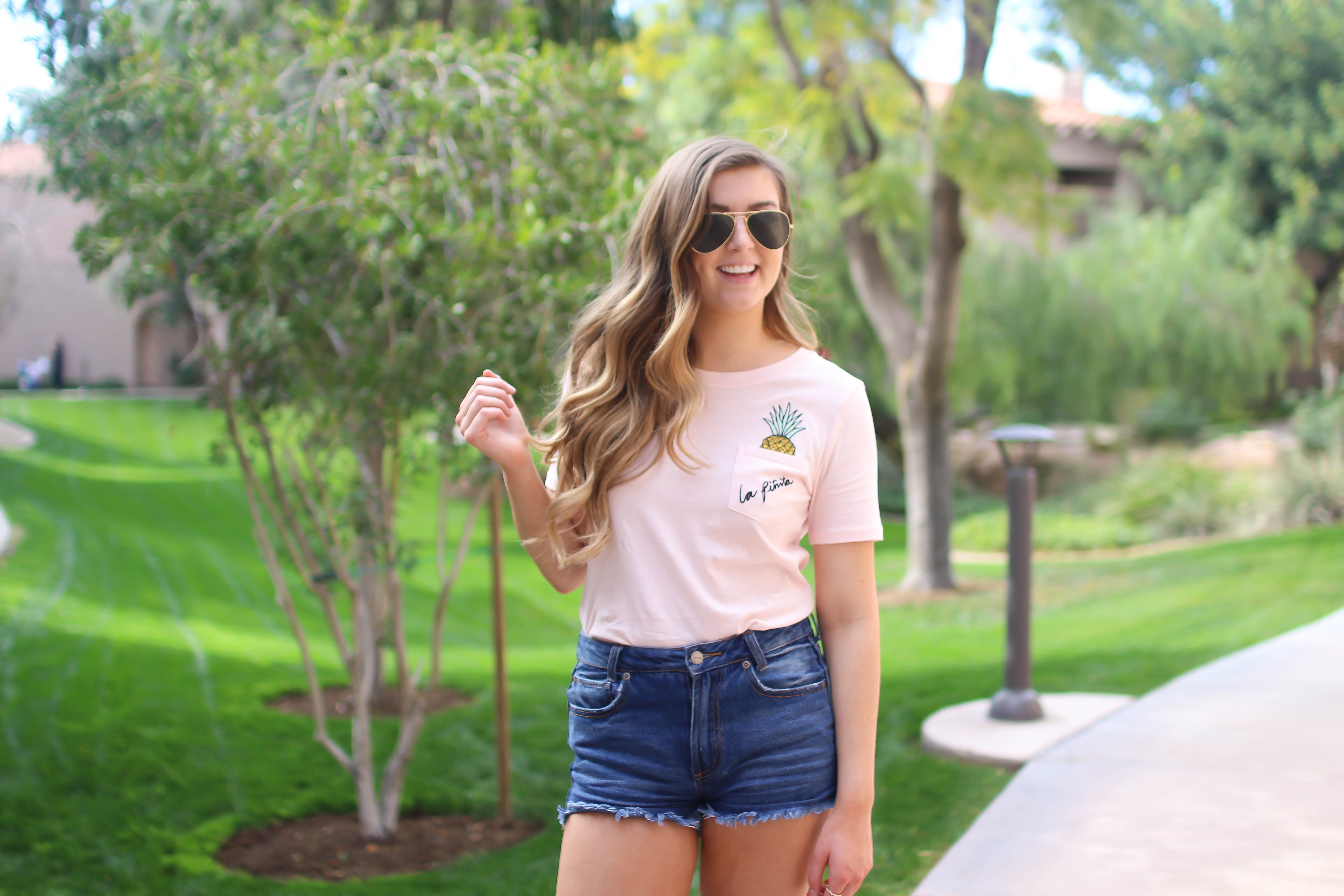 The cutest pink pineapple tee perfect for spring break and summer look! Perfect outfit idea for spring and summer! Paired with jean shorts and Gold New Balance shoes. By Lauren Lindmark on Daily Dose of Charm dailydoseofcharm.com