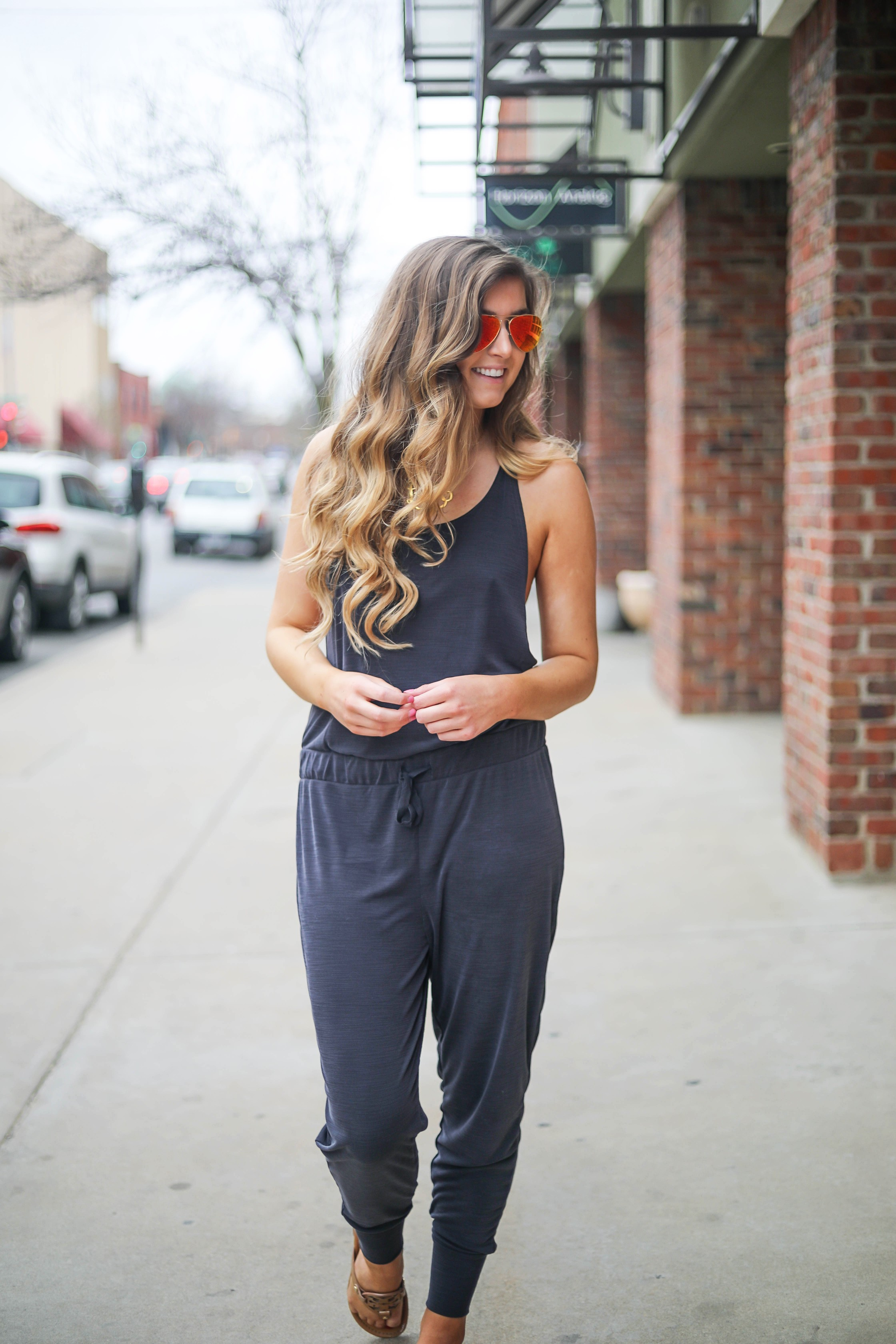 The cutest jumpsuit that is open on the sides and slouchy! I love comfy jumpsuits and this one is my favorite! Paired with red mirrored ray ban aviators and tory burch miller sandals! By Lauren Lindmark dailydoseofcharm.com daily dose of charm