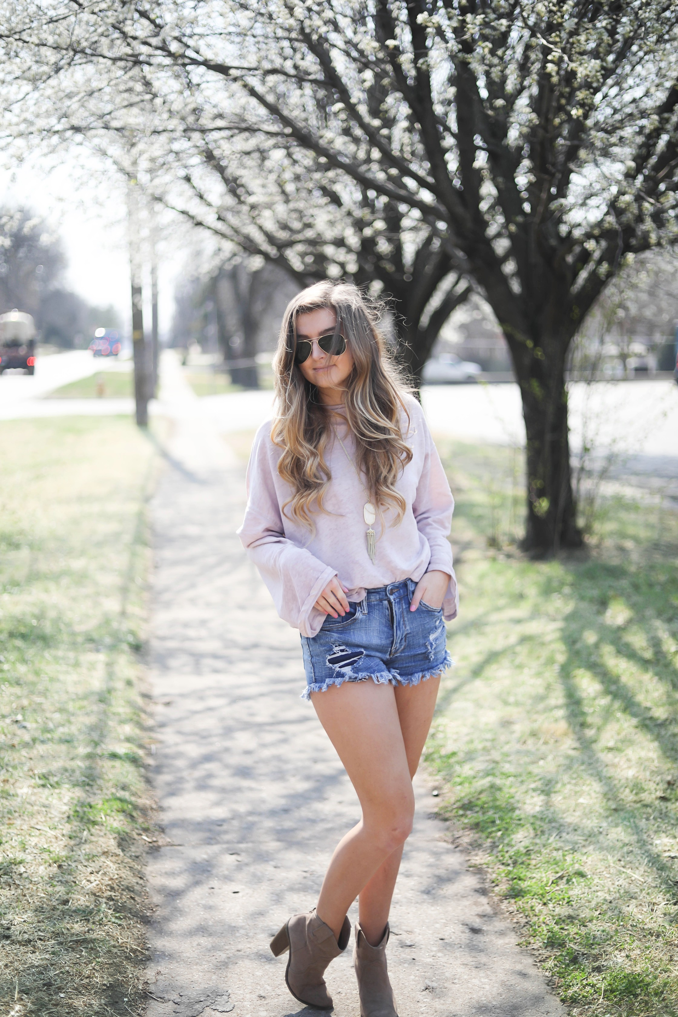 Spring outfit! You can tell it's officially spring when the trees start to bloom! I love this cozy pink top with ripped jeans. I paired them with my favorite booties and white kendra Scott necklace! By Lauren Lindmark dailydoseofcharm.com daily dose of charm