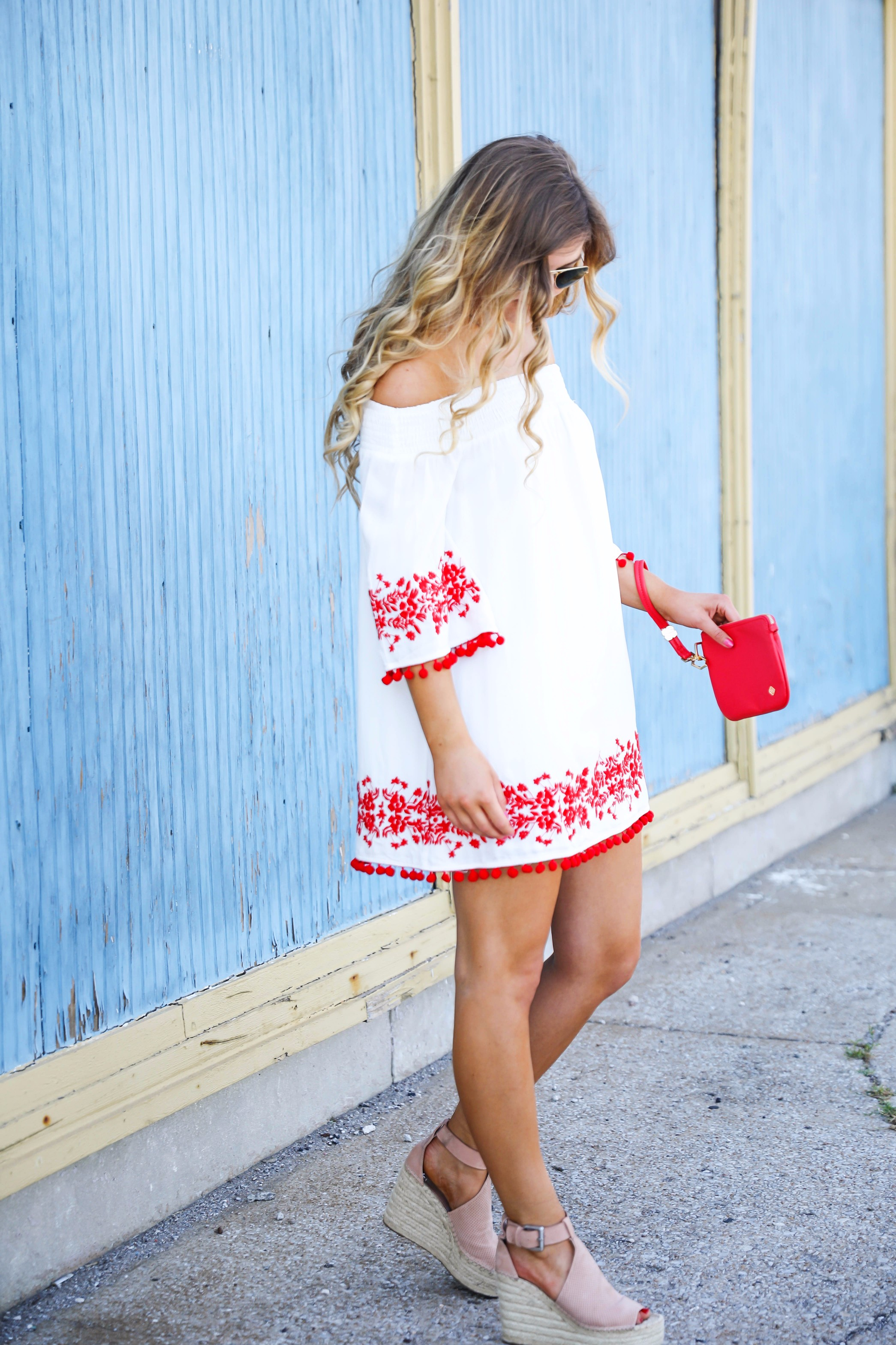 Looking for the perfect fourth of july or summer outfit? This red pom pom off the shoulder dress is so cute with it's embroidered hem! I wore this on the fourth of july! Featured on fashion blog daily dose of charm by lauren lindmark