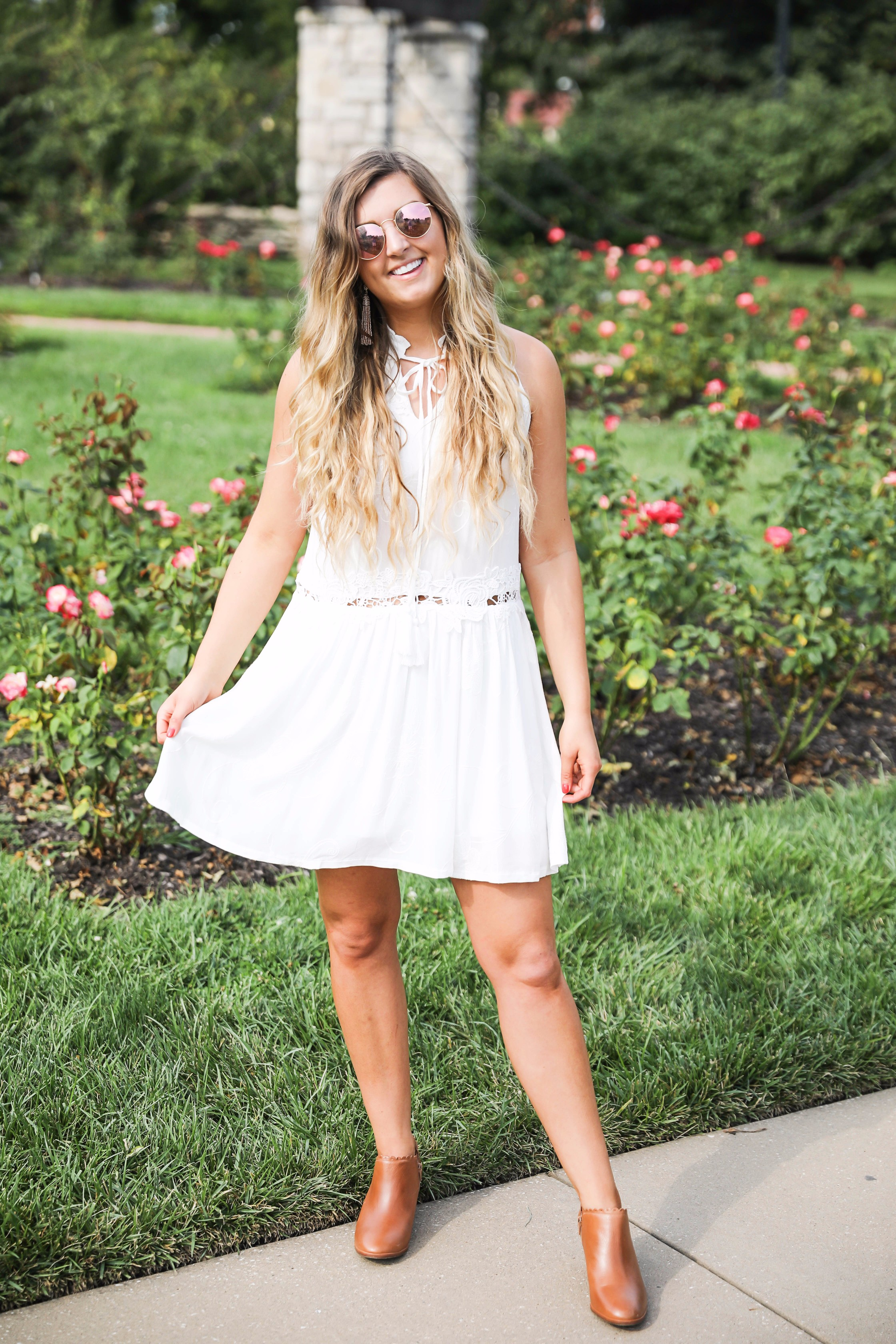 Flowy white dress surrounded by flowers! I love this dress, it's so fun and flowy and it looks so good with booties to transition into fall! Find details on fashion blogger daily dose of charm by lauren lindmark