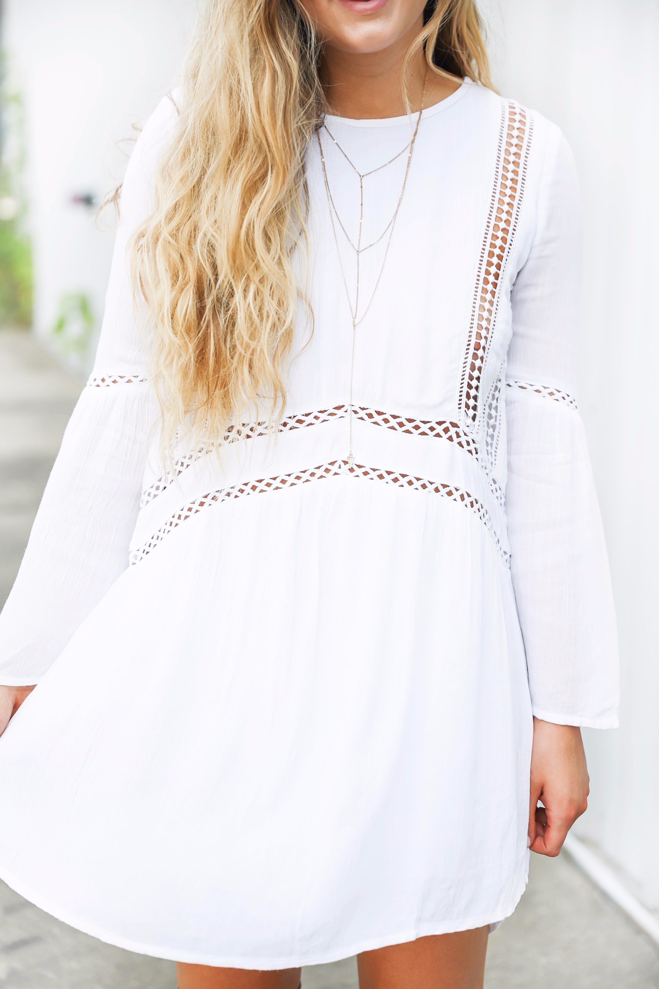 White boho cutout dress with over the knee light brown suede boots! Paired with light blue circle sunglasses. Such a cute dress for summer going into fall! Find the details on fashion blog daily dose of charm by lauren lindmark