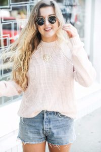 Pink cold shoulder sweater with a large gold monogram necklace and ripped shorts! I love this cute look to transition from summer to fall! Find the details on fashion blog daily dose of charm by lauren lindmark