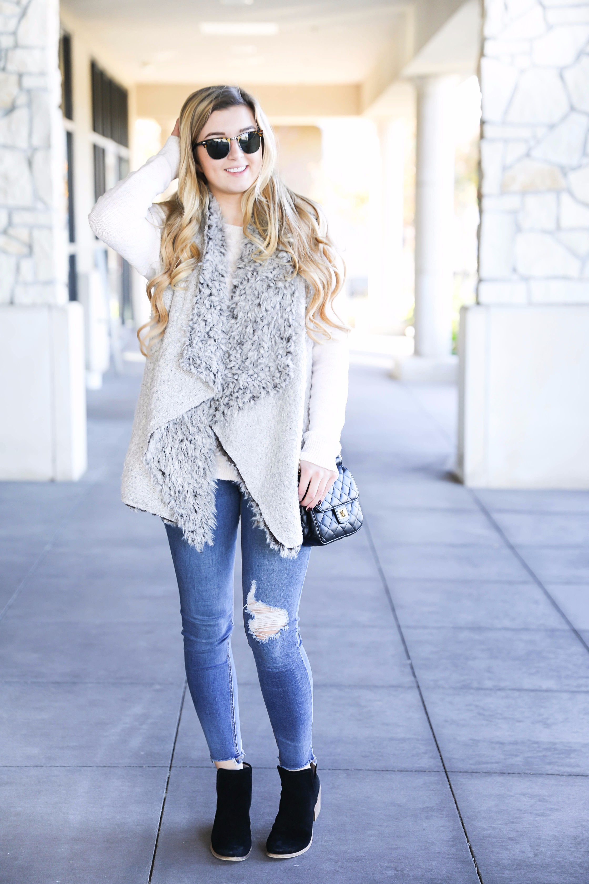 Fuzzy vest with cable knit sweater! Paired with my favorite ripped jeans and clubmaster sunglasses. These black booties are the best! Details on fashion blog daily dose of charm by lauren lindmark