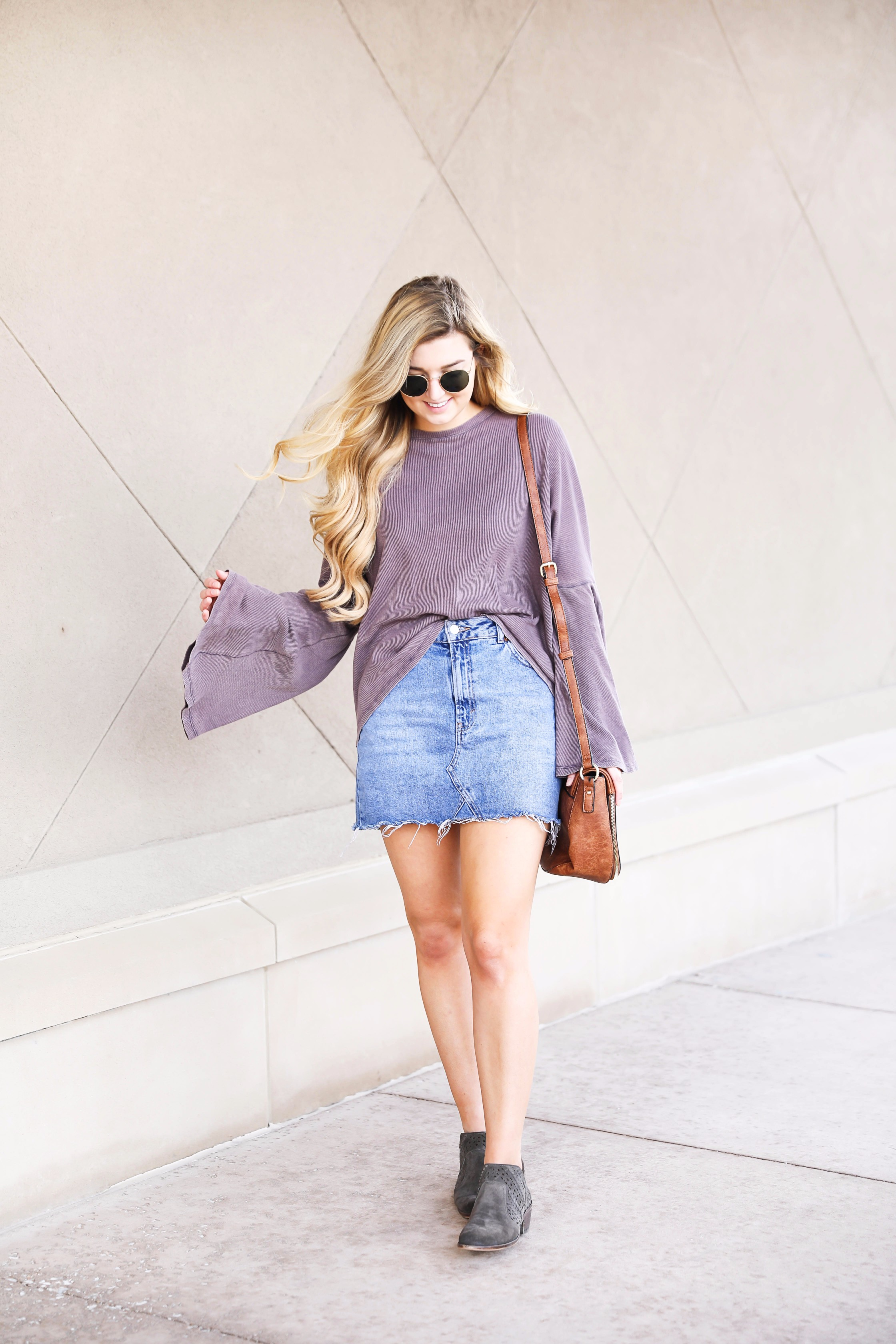 Purple bell sleeve top with jean skirt and saddle bag! Paired with cutout booties! Find the details on fashion blog daily dose of charm by lauren lindmark