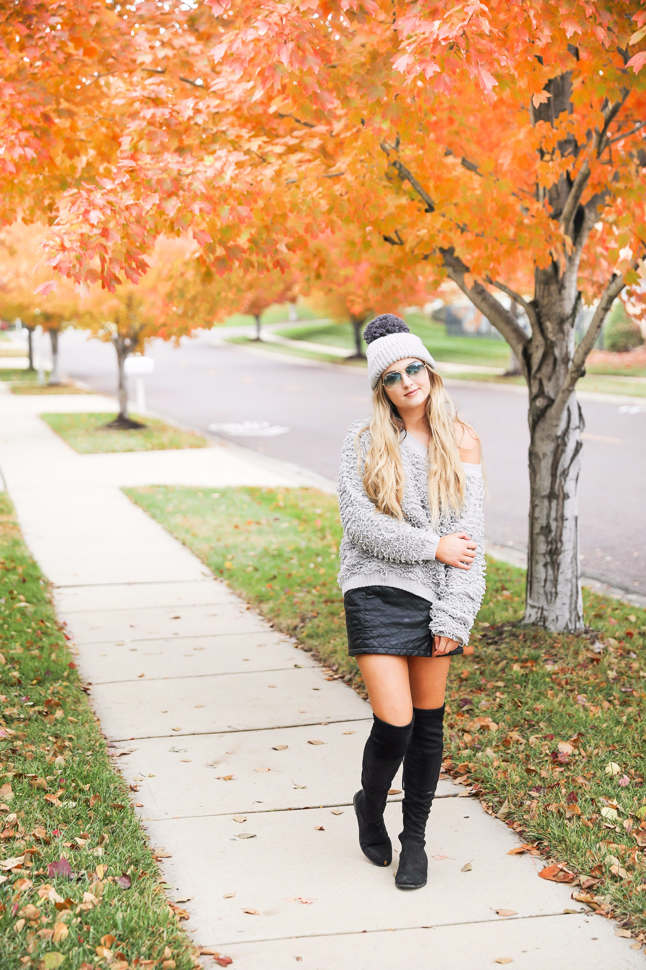 Grey loop sweater with black faux leather skirt and over the knee black boots! Paired with a pom beanie for colder days. Such a cute fall and winter outfit! Find the details on fashion blog daily dose of charm by lauren lindmark