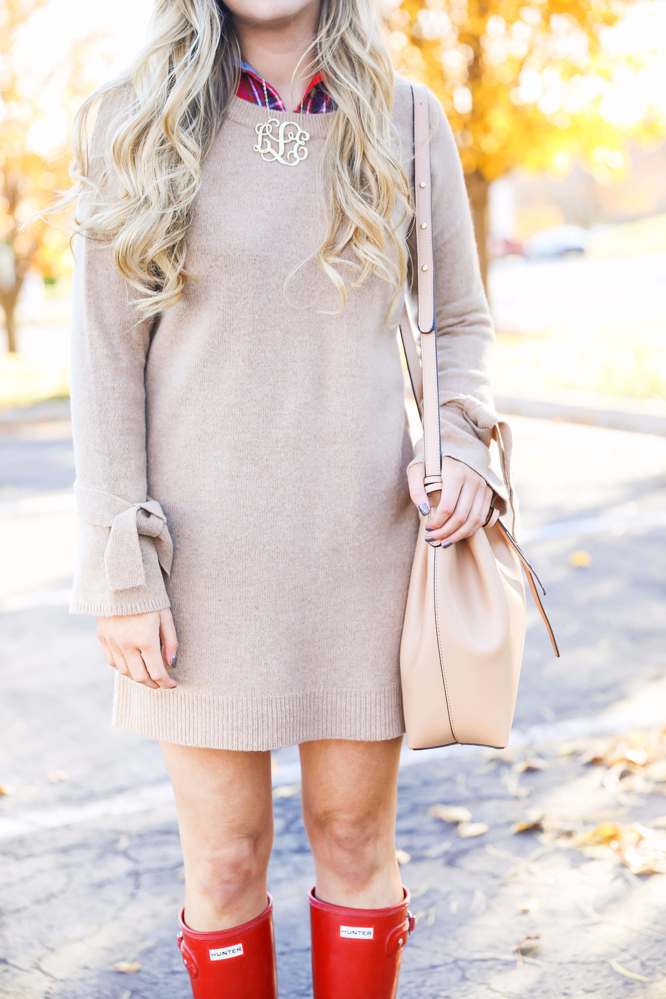 Thanksgiving outfit idea tan dress with tied sleeves! Layered with flannel underneath! I love this fall outfit with hunter boots! Details on fashion blog daily dose of charm by lauren lindmark