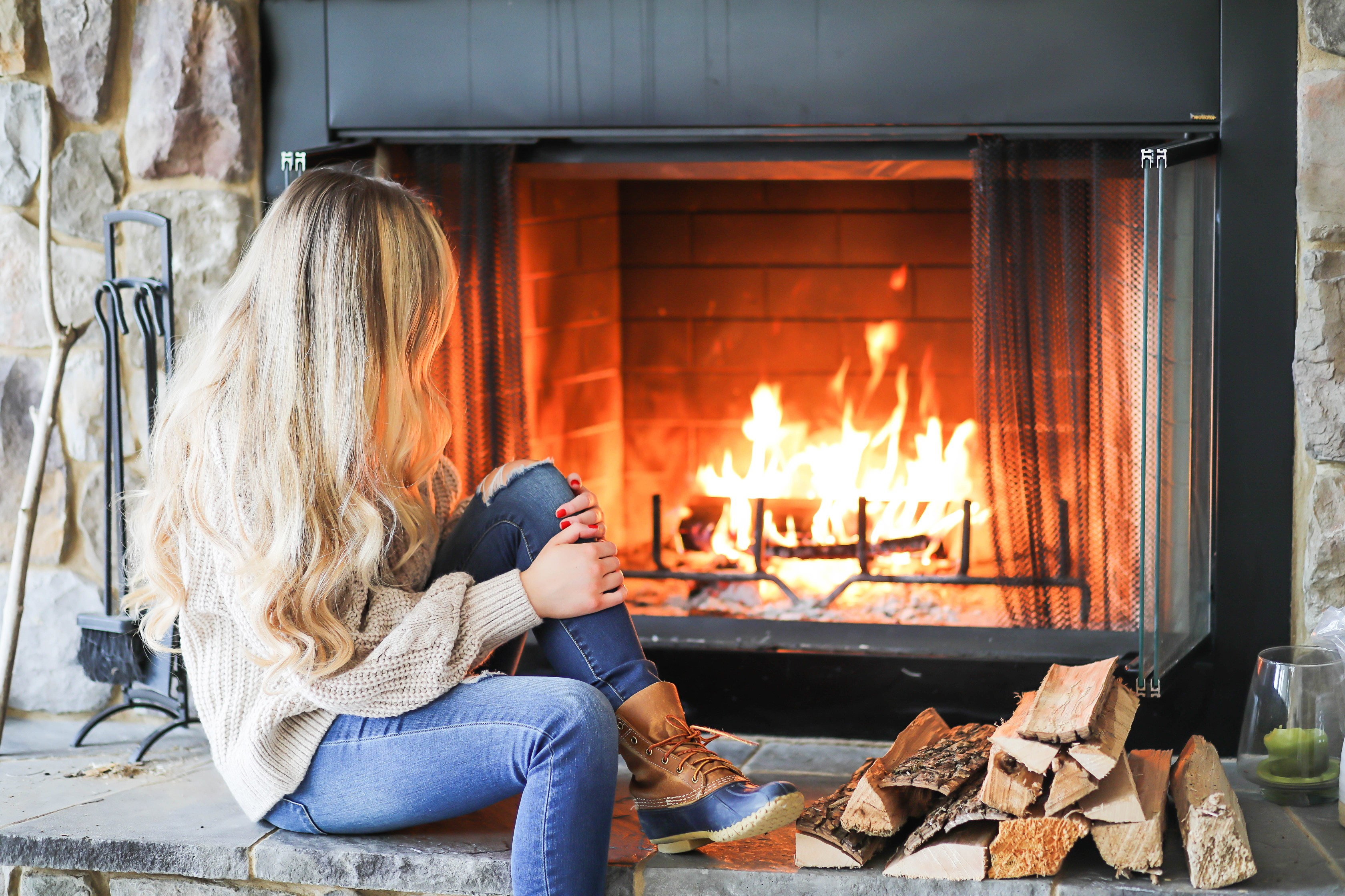 Cozy cable knit sweater in front of stone fireplace! This winter cable knit sweater is so cute and the fire looks so inviting! I paired it with my L.L. Bean duck Boots! Details on fashion blog daily dose of charm by lauren lindmark