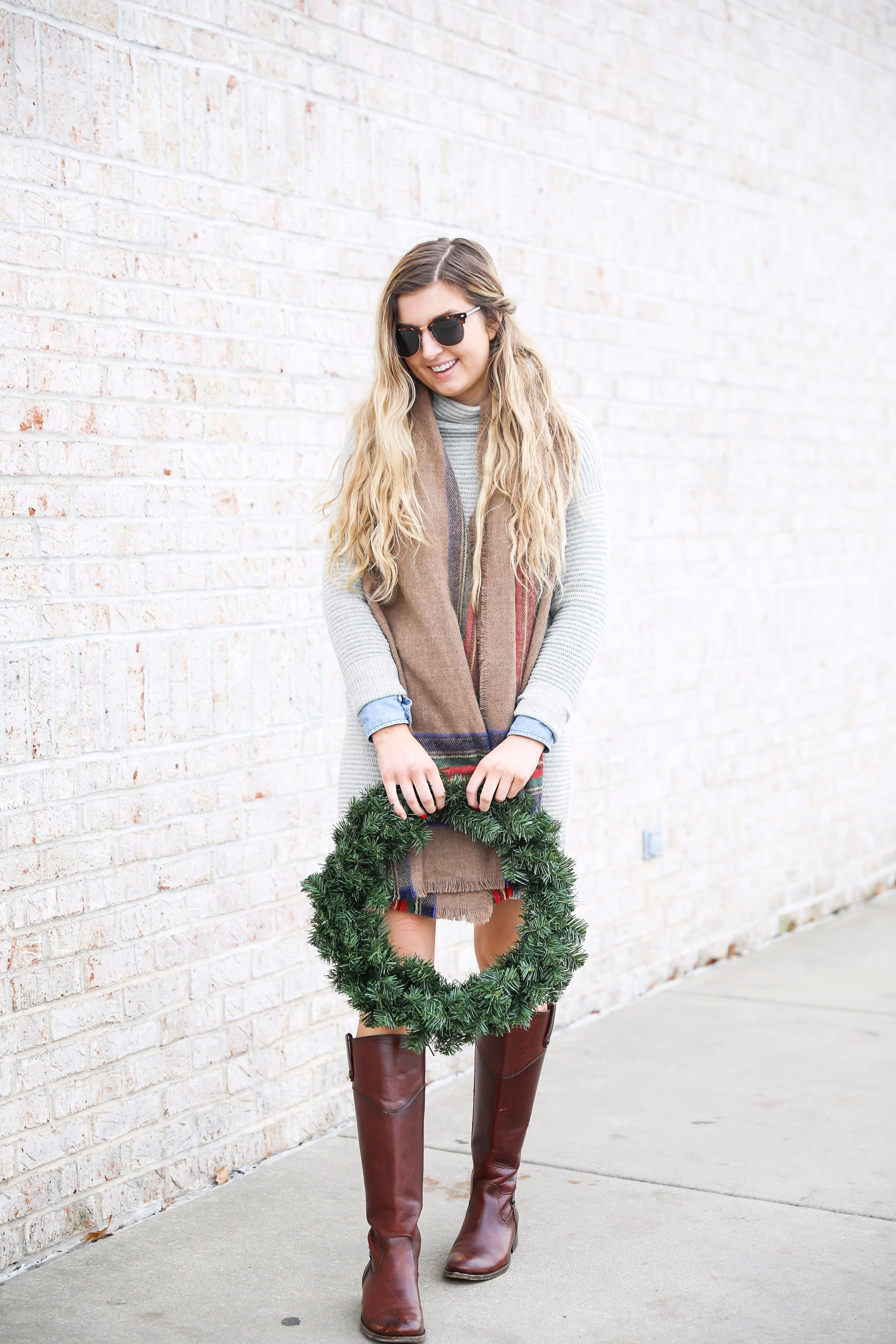 Grey sweater dress layered wtih a chambray top and plaid scarf! Paired with my favorite riding boots by frye boots! Photos taken with a christmas wreath. Christmas wreath photos by lauren lindmark on the blog daily dose of charm
