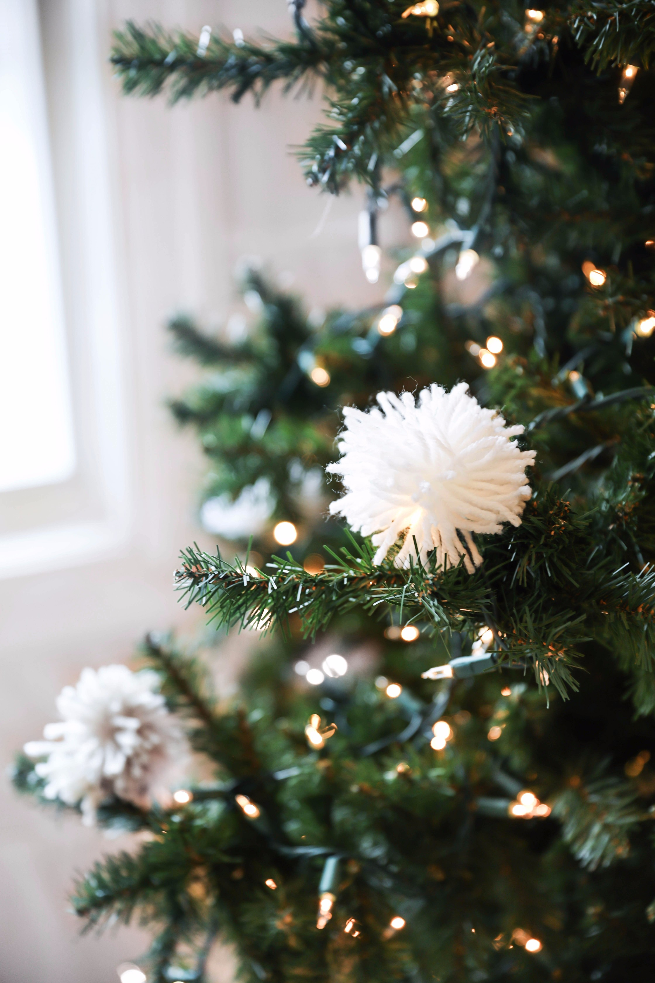 Holiday DIY decor! Learn how to make DIY snowball ornaments, tassel ornaments, pom pom ornaments, pom pom pillows, and pom pom garlands! Details on daily dose of charm lauren lindmark