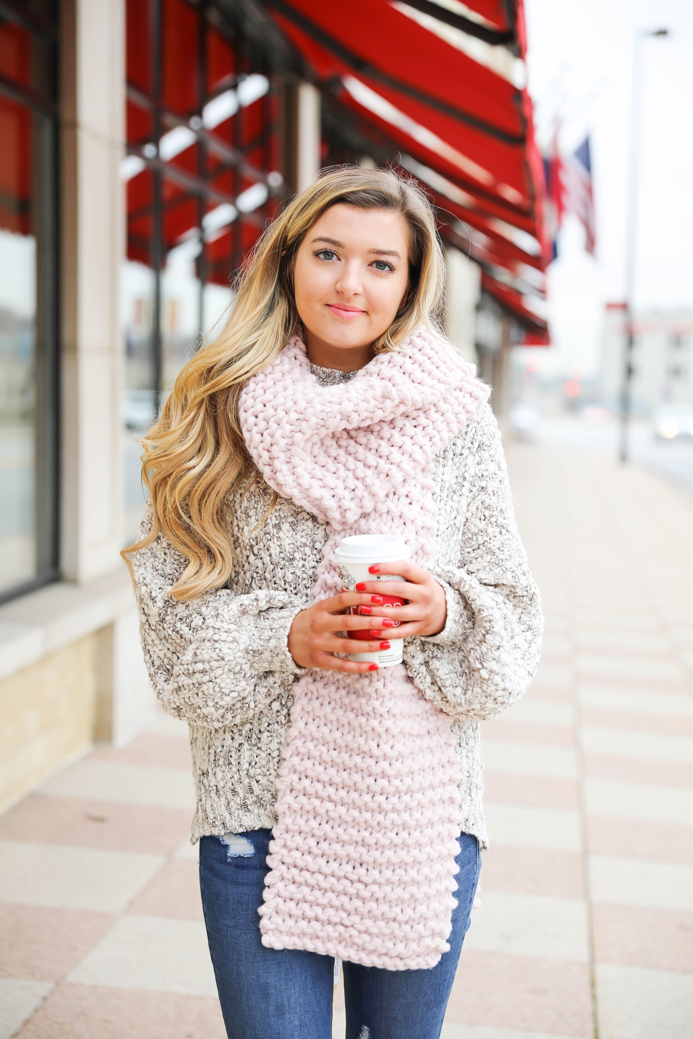 Huge knit scarf and cozy knit sweater with frye riding boots! Such a super cute winter outfit idea! Red cup from Starbucks with a cute winter outfit! Details on fashion blog daily dose of charm lauren lindmark