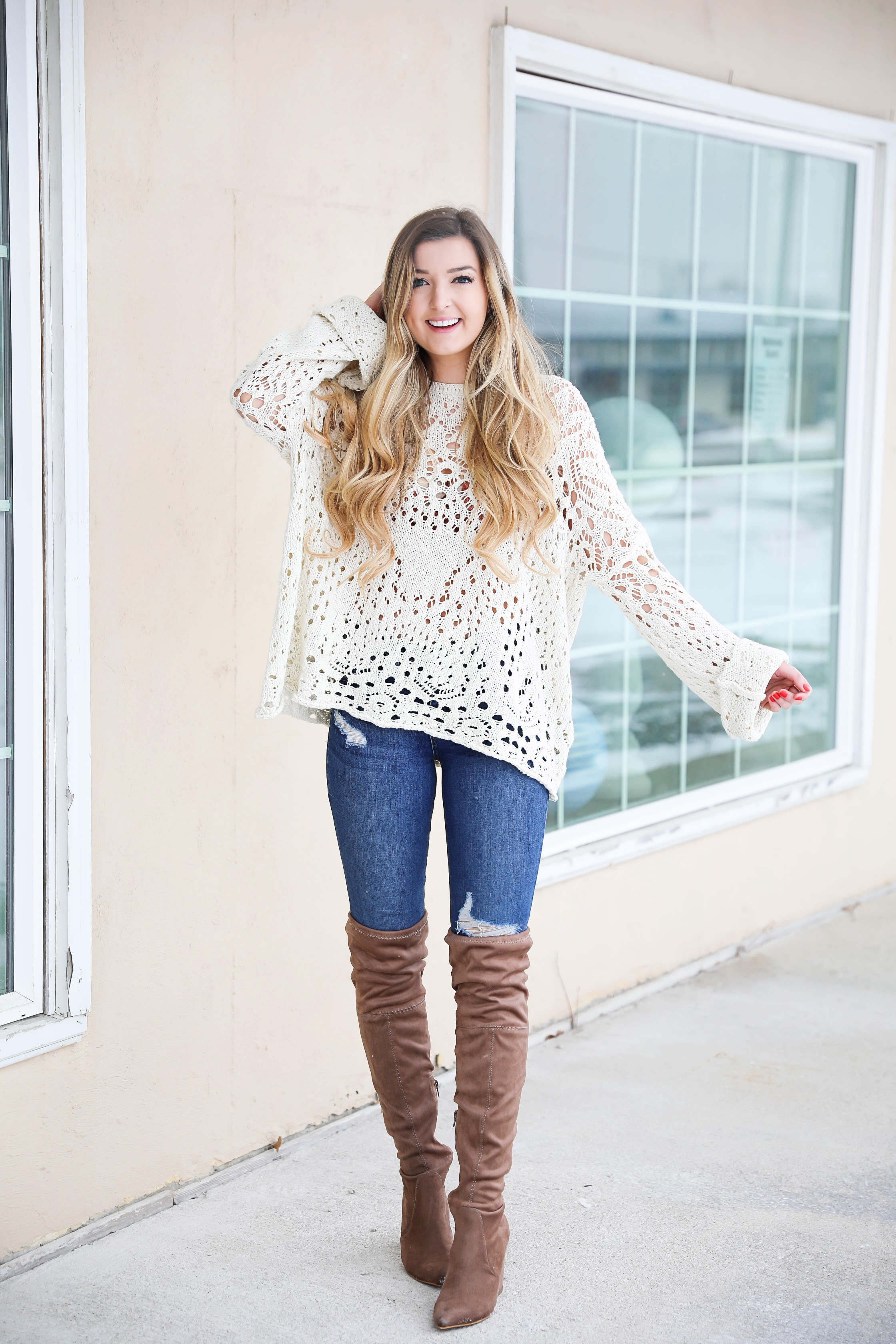 Free People crochet sweater and rust orange bralette peaking through the sweater! Love it with these over the knee boots and ripped denim jeans! Find the details on fashion blog daily dose of charm by lauren lindmark