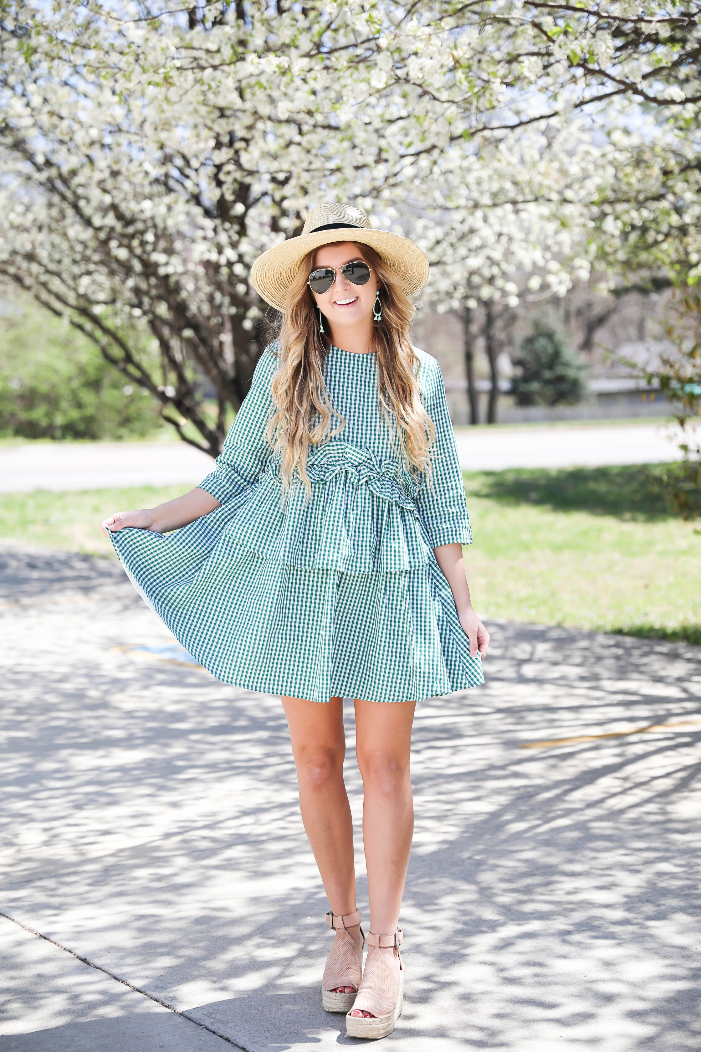 Green gingham dress perfect for spring days or days on the beach! I paired it with a straw hat and blue earrings! The most beautiful spring blooming trees were in the background making this spring fashion look perfection! Details on fashion blog daily dose of charm by lauren lindmark