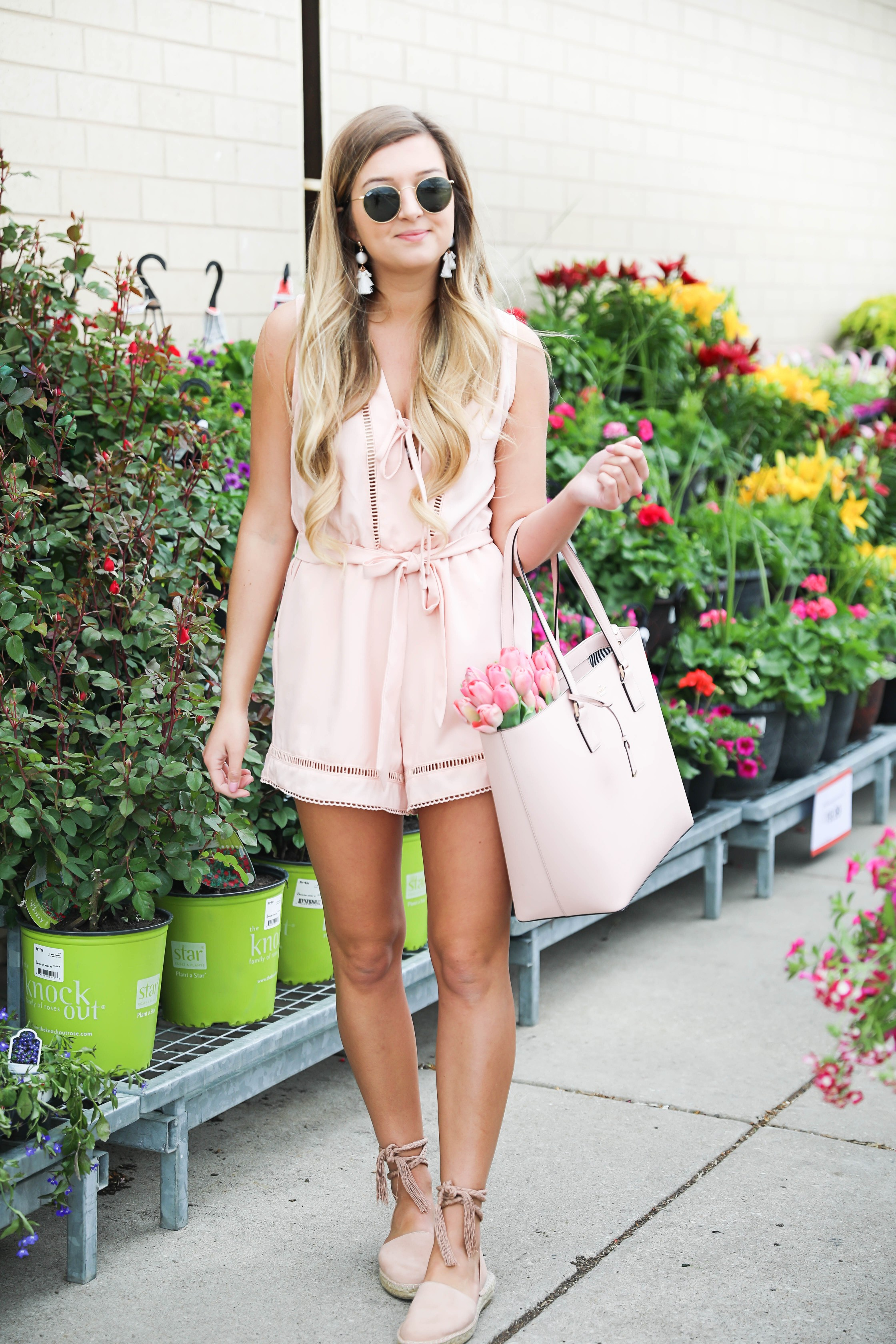 Pink romper with a cinched waist paired with a pink Kate Spade tote with flowers! These photos were taken at a flower nursery! Such a cute spring outfit, details on fashion blog daily dose of charm by lauren lindmark