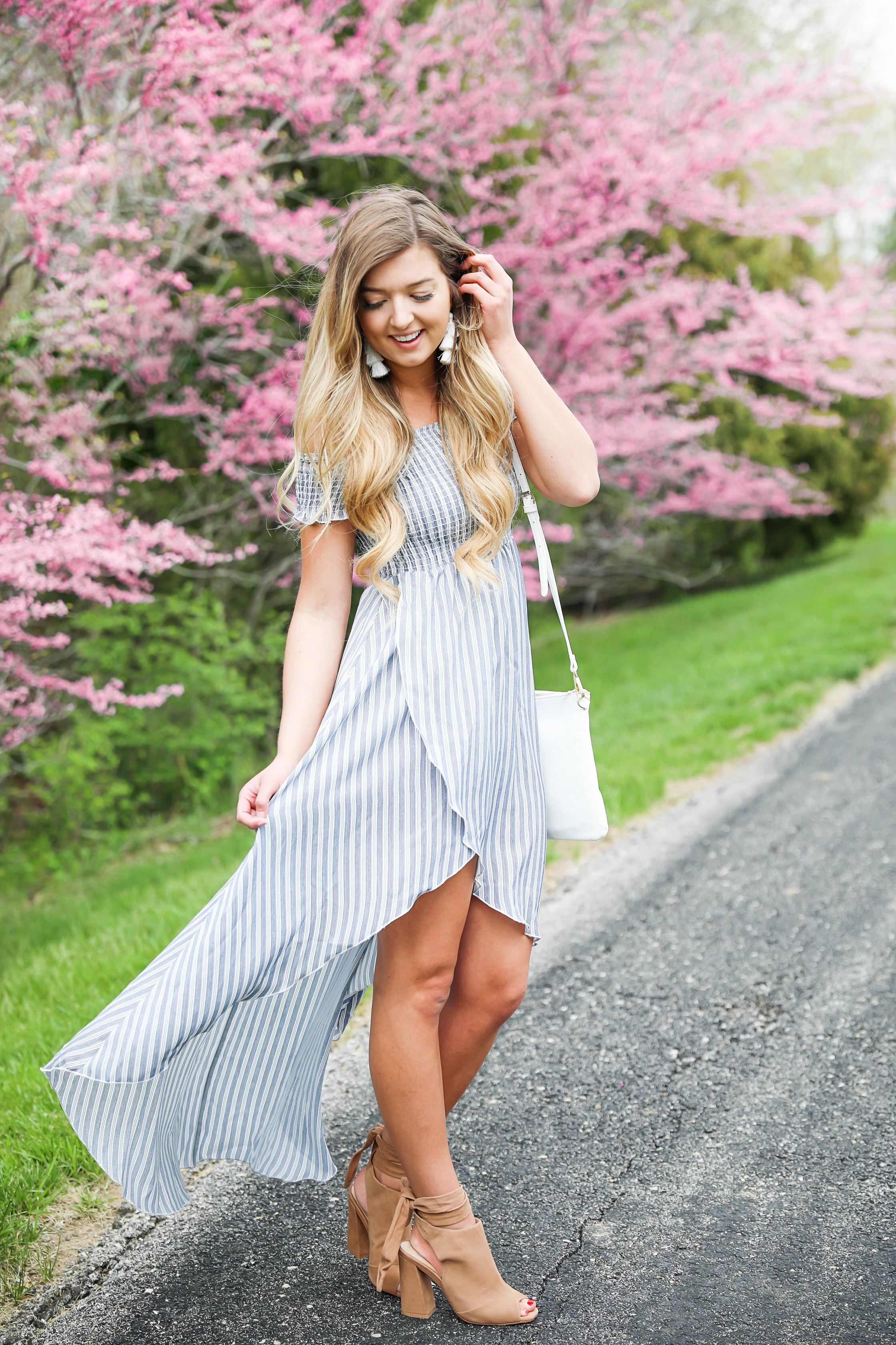 Show me your mumu striped high low maxi dress! Paired with adorable tie up heels and tassel earrings! Springy pink flower trees tie together this whole photoshoot! Check out this spring outfit on fashion blog daily dose of charm by Lauren Lindmark
