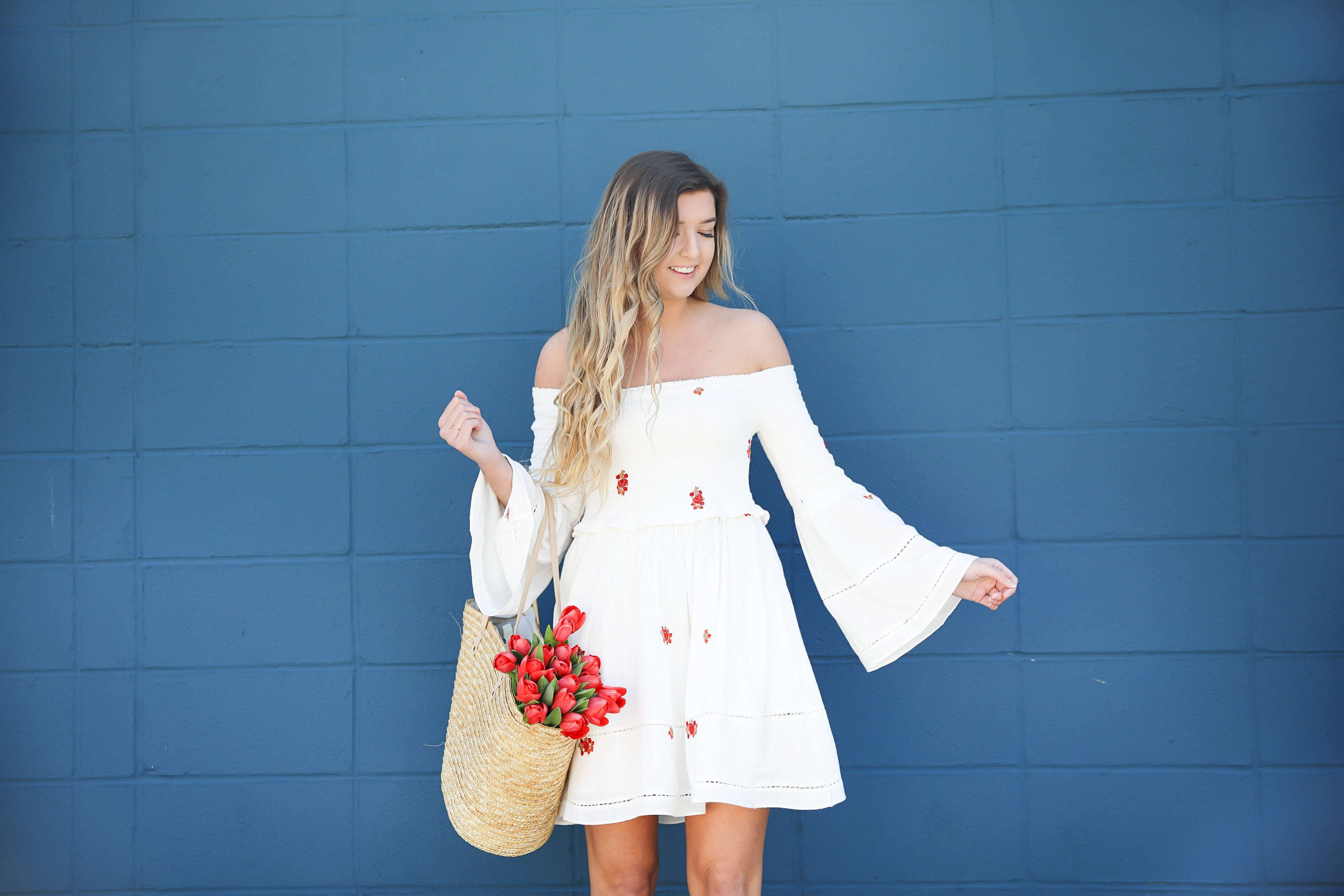 White off the shoulder dress with red embroidery by Free People! Love this look with red tulips in a straw bag and cute wedges! Perfect spring look on fashion blog daily dose of charm by lauren lindmark