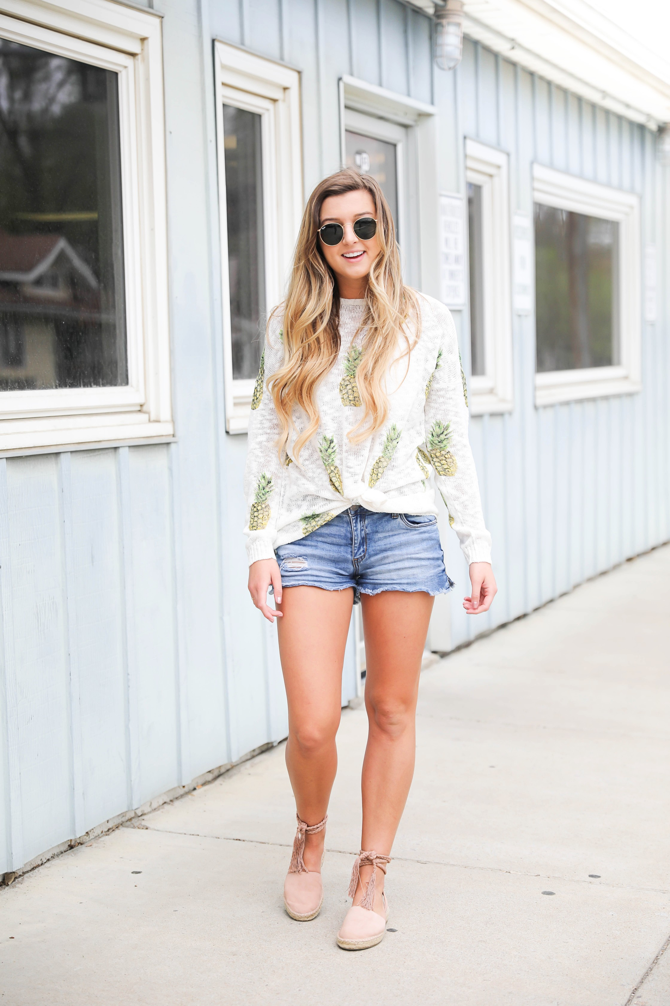 Cute pineapple sweater tucked into denim shorts for spring! Show Me Your Mumu pineapple sweater! I love this spring outfit, this adorable spring sweater is on fashion blog daily dose of charm by lauren lindmark