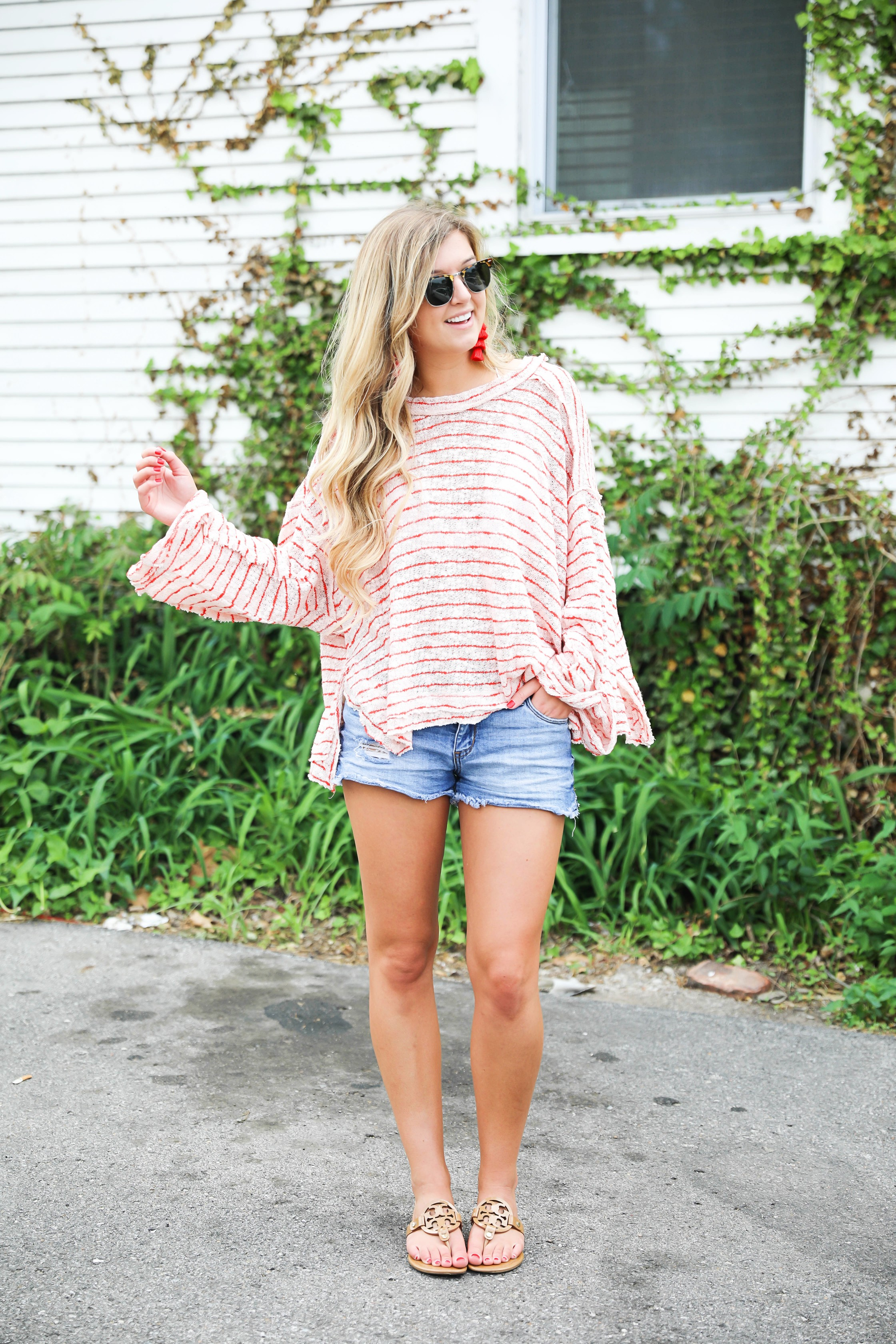 Striped red free people sweater with denim shorts and red tassel earrings! Perfect sweater for summer and days at the beach! Light weight summer sweater! Fourth of july outfit idea on fashion blog daily dose of charm by lauren lindmark