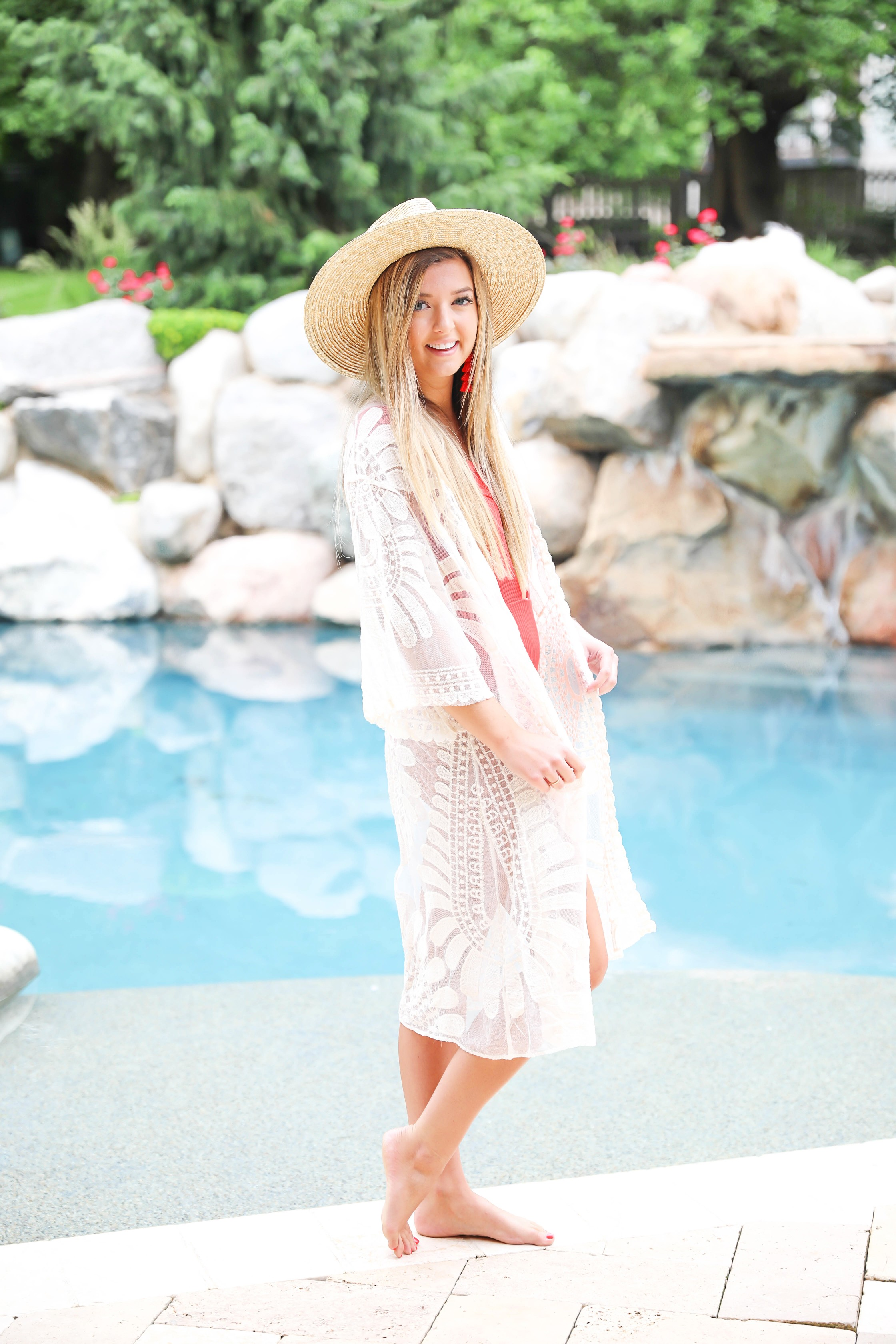 Hot red one piece! This adorable suit is reversible and also comes in white, yellow, and black! I paired this with my sheer mesh woven lace kimono and wide brim straw hat! Summer look by the pool! Details on fashion blog daily dose of charm by lauren lindmark