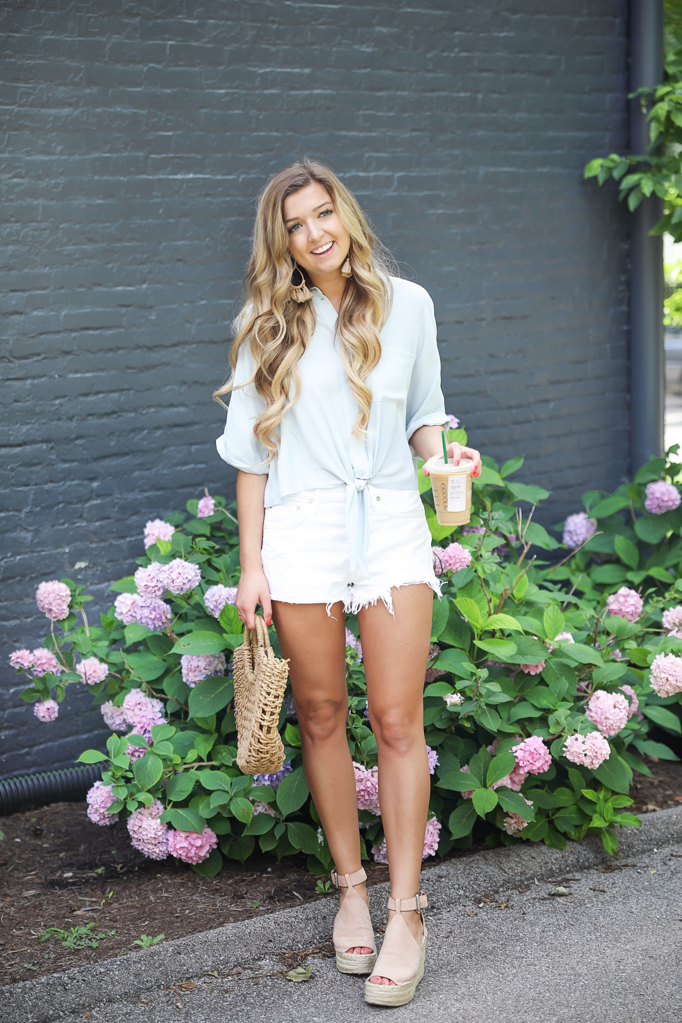 Light blue tied top paired with white denim cut off shorts! Cute straw beach bag with marc fisher wedges! I love starbucks iced coffees with my outfits! I shot this in front of some pretty hydrangeas in Lexington, Kentucky! Details on daily dose of charm lauren lindmark