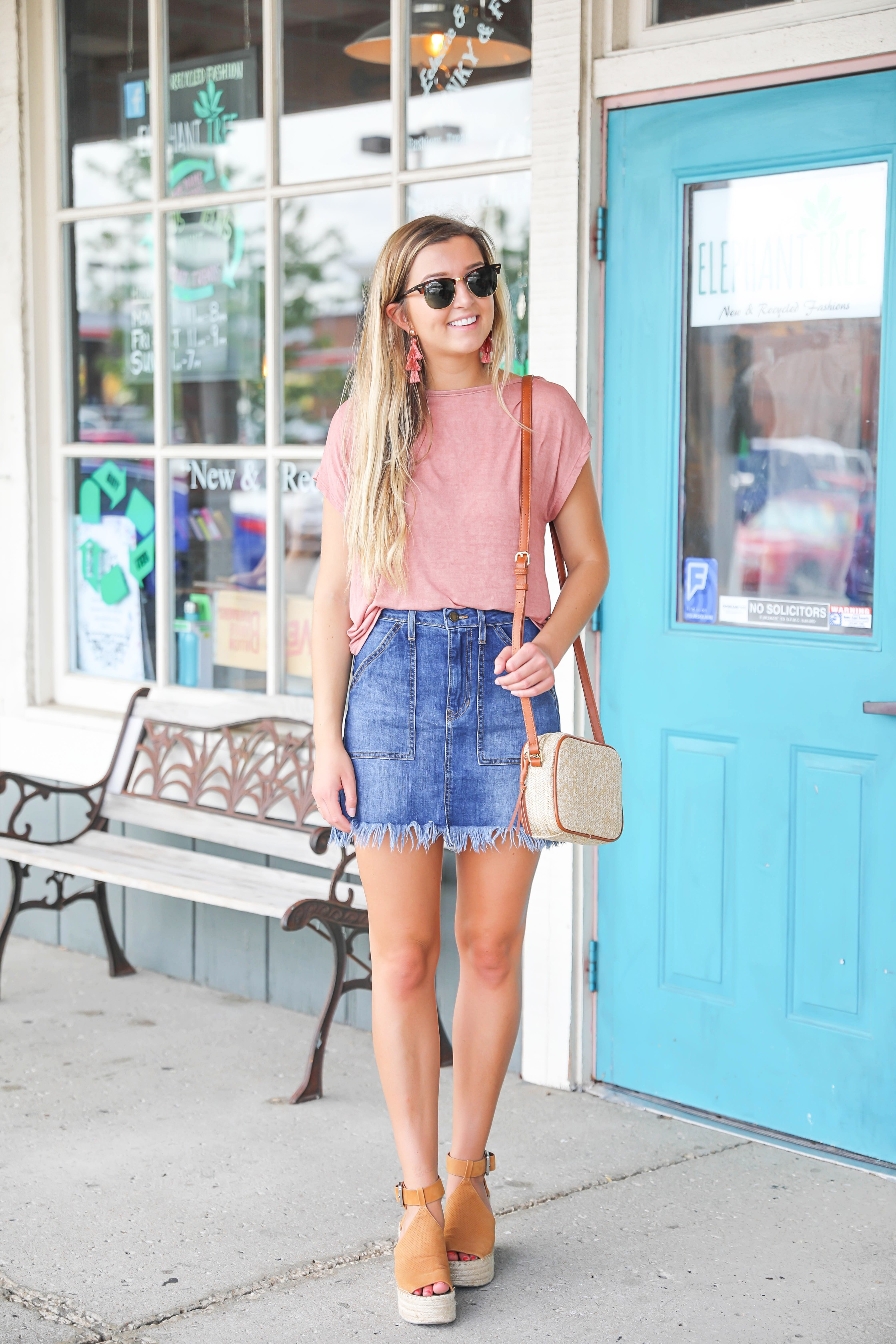 Open back tops are so cute in the summer! This cinched and tied coral top is so cute with this frayed jean skirt! I finished off the look with my straw bag and marc fisher wedges! Details on this summer outfit are on fashion blog daily dose of charm by lauren lindmark