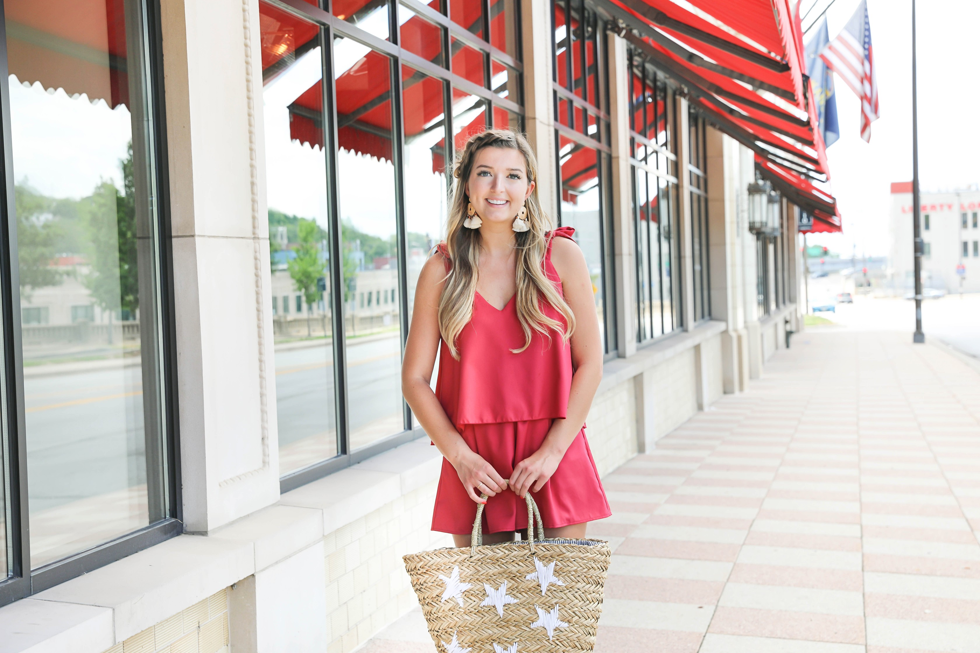 Red romper with cute tied shoulders! The cutest summer romper for Fourth of July! Paired with a star beach bag for fourth of July! Outfit details on fashion blog daily dose of charm by lauren lindmark