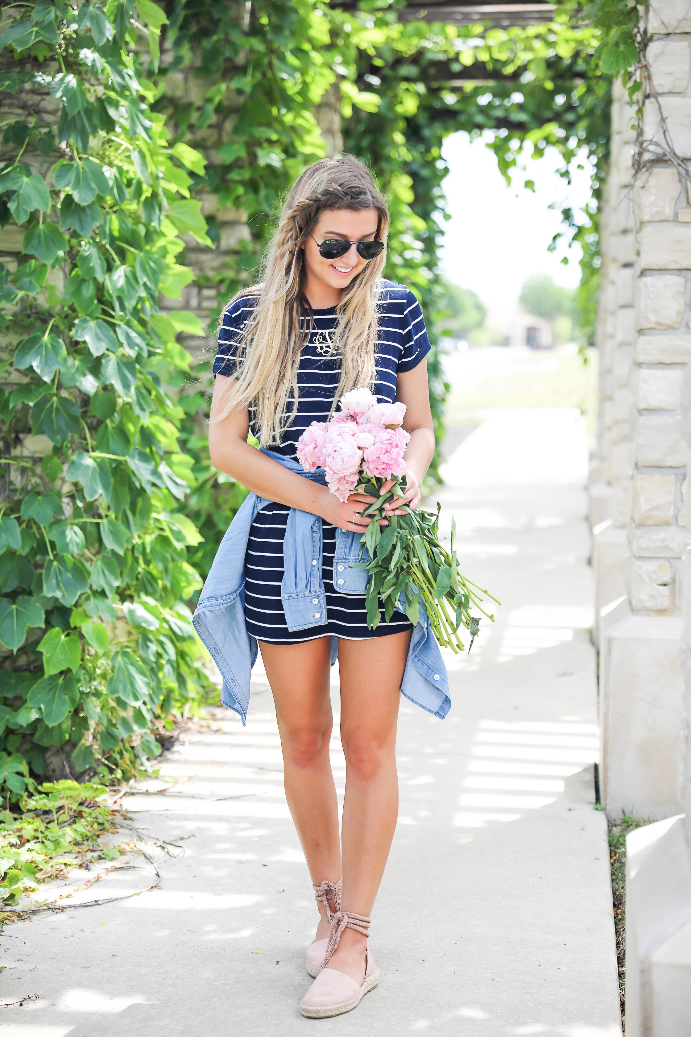 "Striped t-shirt dress with a jean jacket tied around my waist! I love these pink peonies in the summer so they made the perfect ""accessory"" to this look! I finished the outfit with my braided suede shoes and large gold monogram necklace! Plus my new favorite Ray Ban black aviators! Details on this summer outfit are on fashion blog daily dose of charm by lauren lindmark"