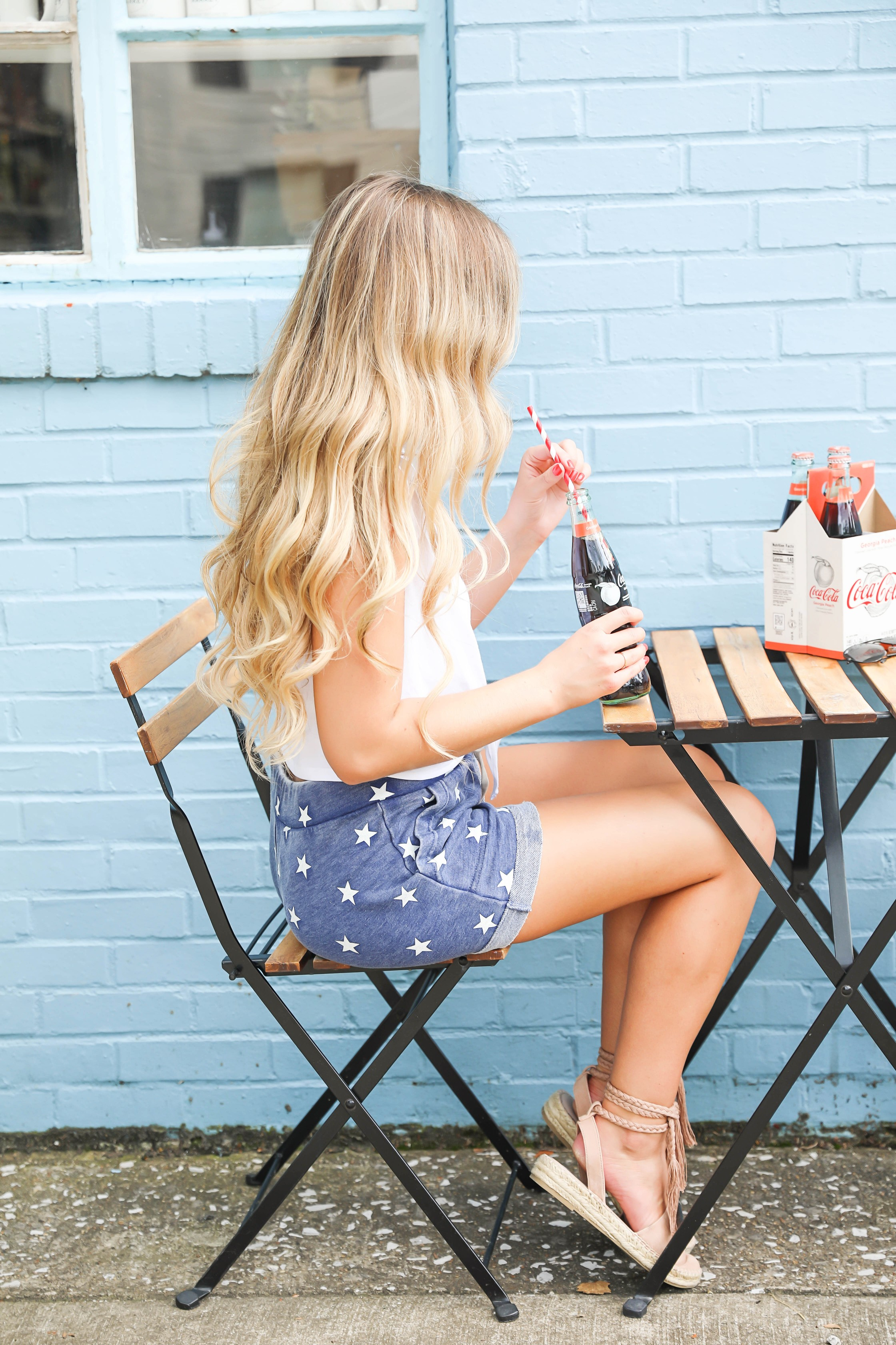 Fourth of july outfit inspo! I love these comfy blue star shorts! I paired it with this cute tied top! Such a fun coke bottle photoshoot! Red, white, and blue outfit details on fashion blogger daily dose of charm by lauren lindmark