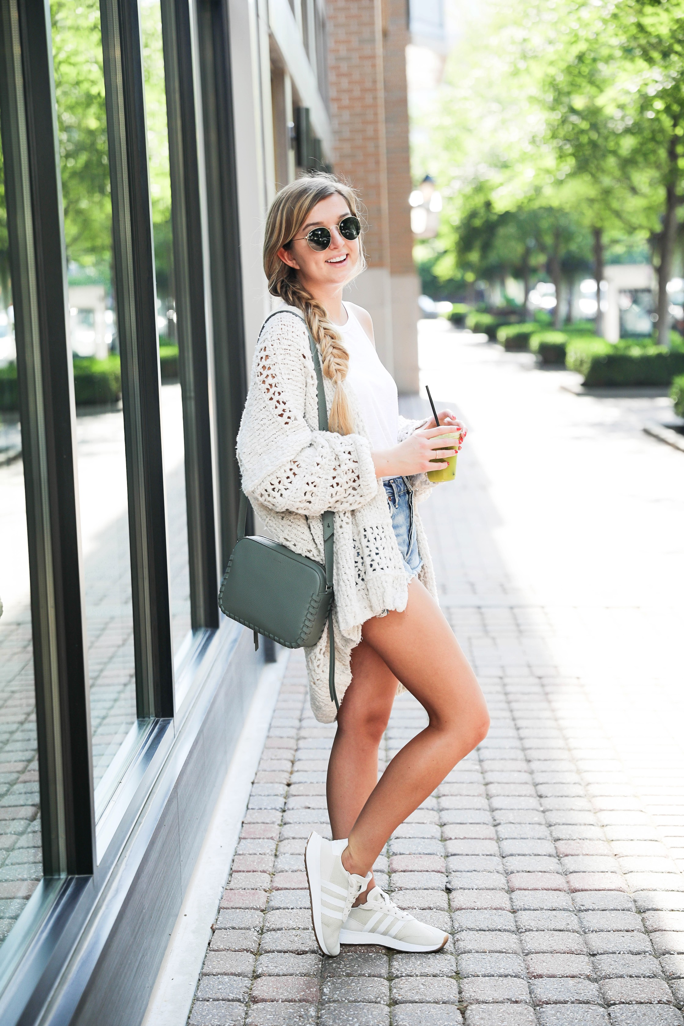Free People crochet cardigan that comes in three colors! I paired mine with my cute agolde distressed denim jean shorts and allsaints crossbody bag! The cardigan and bag are included in the Nordstrom Anniversary Sale 2018! Finished off the look with my Adidas sneakers and a T.Loft Juice! Details on fashion blog daily dose of charm by lauren lindmark