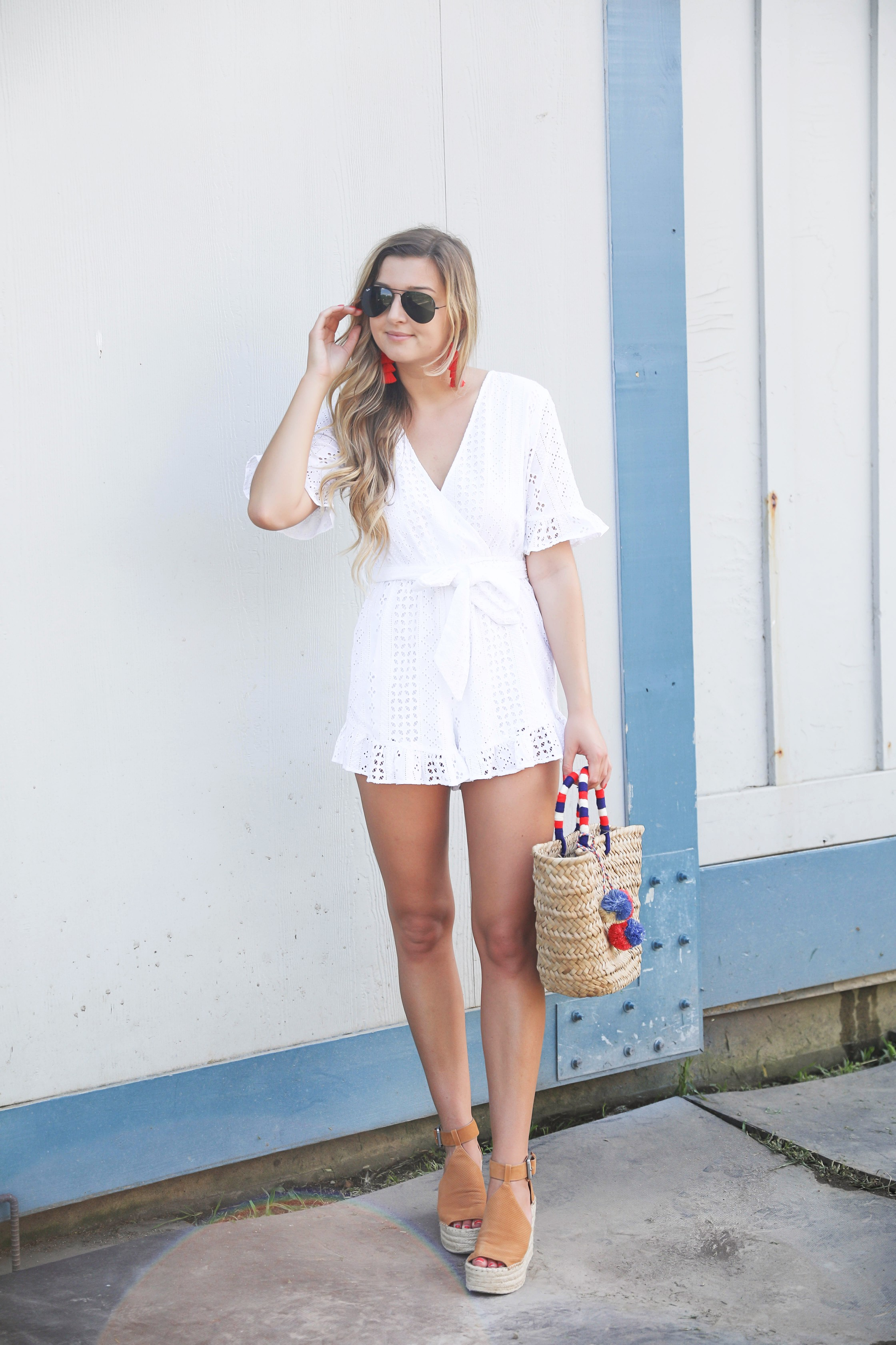 White ruffle tied romper perfect for dressing up or dressing down! Paired with a cute straw beach bag for fourth of july! The beach bag has red white and blue pom poms on it! I finished the fourth of july outfit with red tassel earrings and my favorite wedges! Details on fashion blog daily dose of charm by lauren lindmark