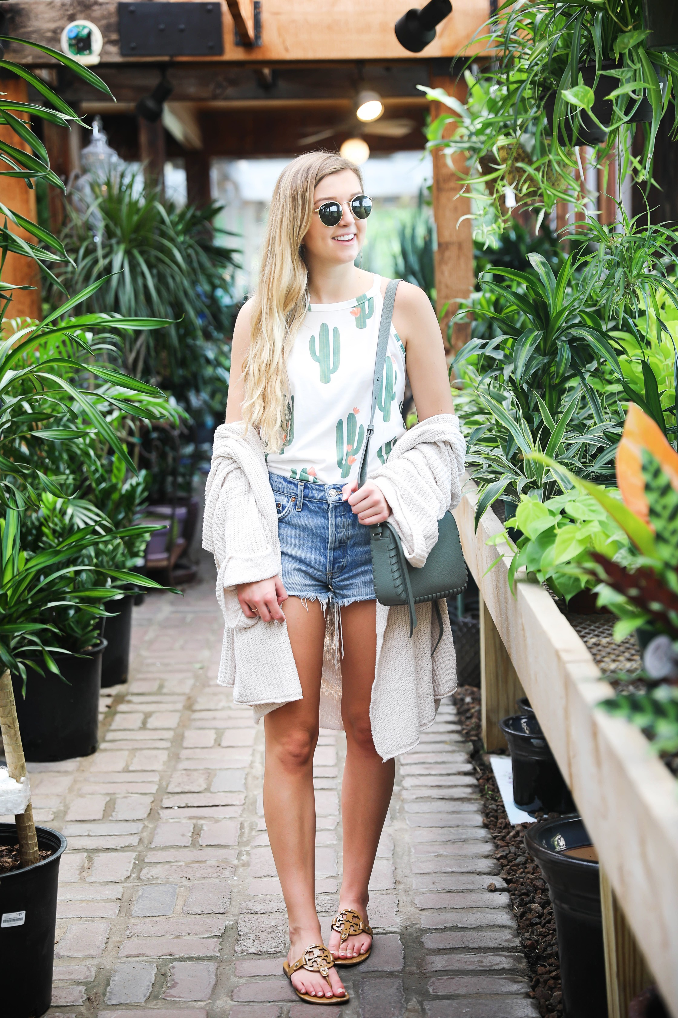Cutest cactus top! Not only is it adorable, but it's inexpensive! I paired them with jean shorts, my favorite cream free people cardigan, my new allsaints bag, Tory Burch Millers, and Ray Ban sunglasses! The cutest summer outfit shot at a flower and plant nursery! Details on fashion blog daily dose of charm by lauren lindmark