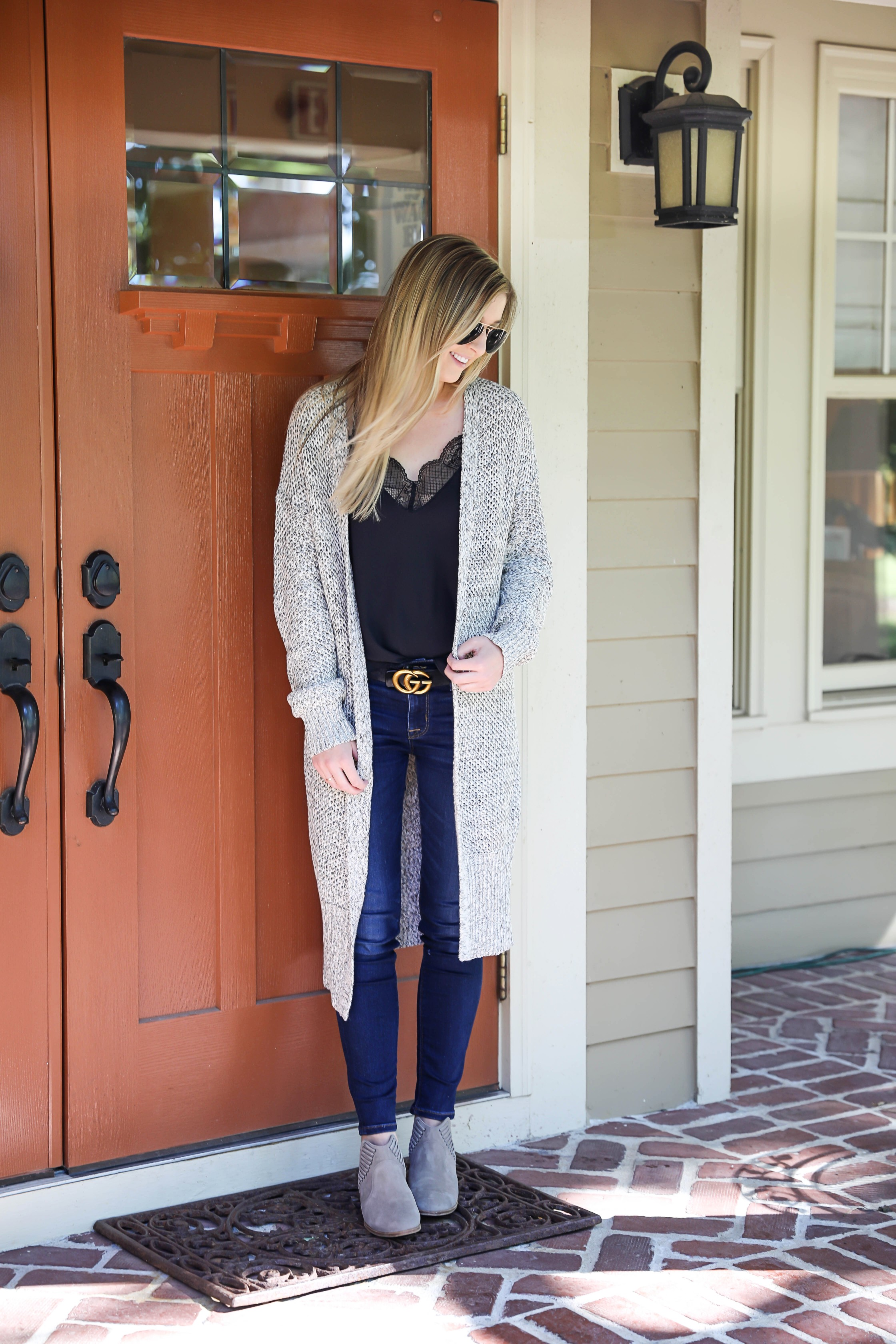 Black cami with long grery knitted duster! Perfect fall outfit paired with a cute gucci belt and dark denim jeans! I am also wearing my vince camuto booties that I love for autumn! Details on fashion blog daily dose of charm by lauren lindmark