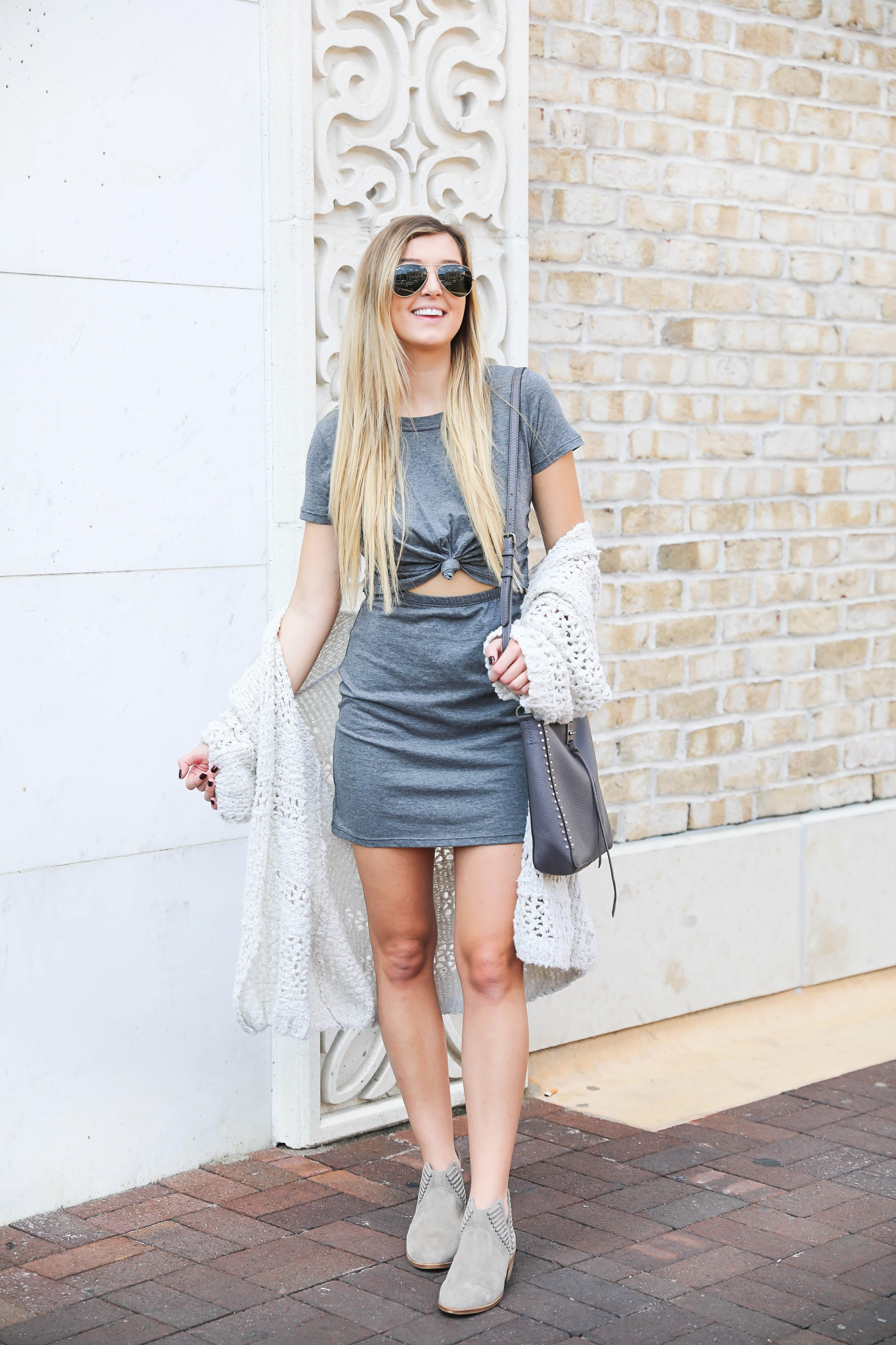 Fitted grey tied tshirt dress and free people cream cardigan! Paired with cute Vince Camuto grey booties and rebecca minkoff gray studded bag! The cutest fall outfit on fashion blog daily dose of charm by lauren lindmark