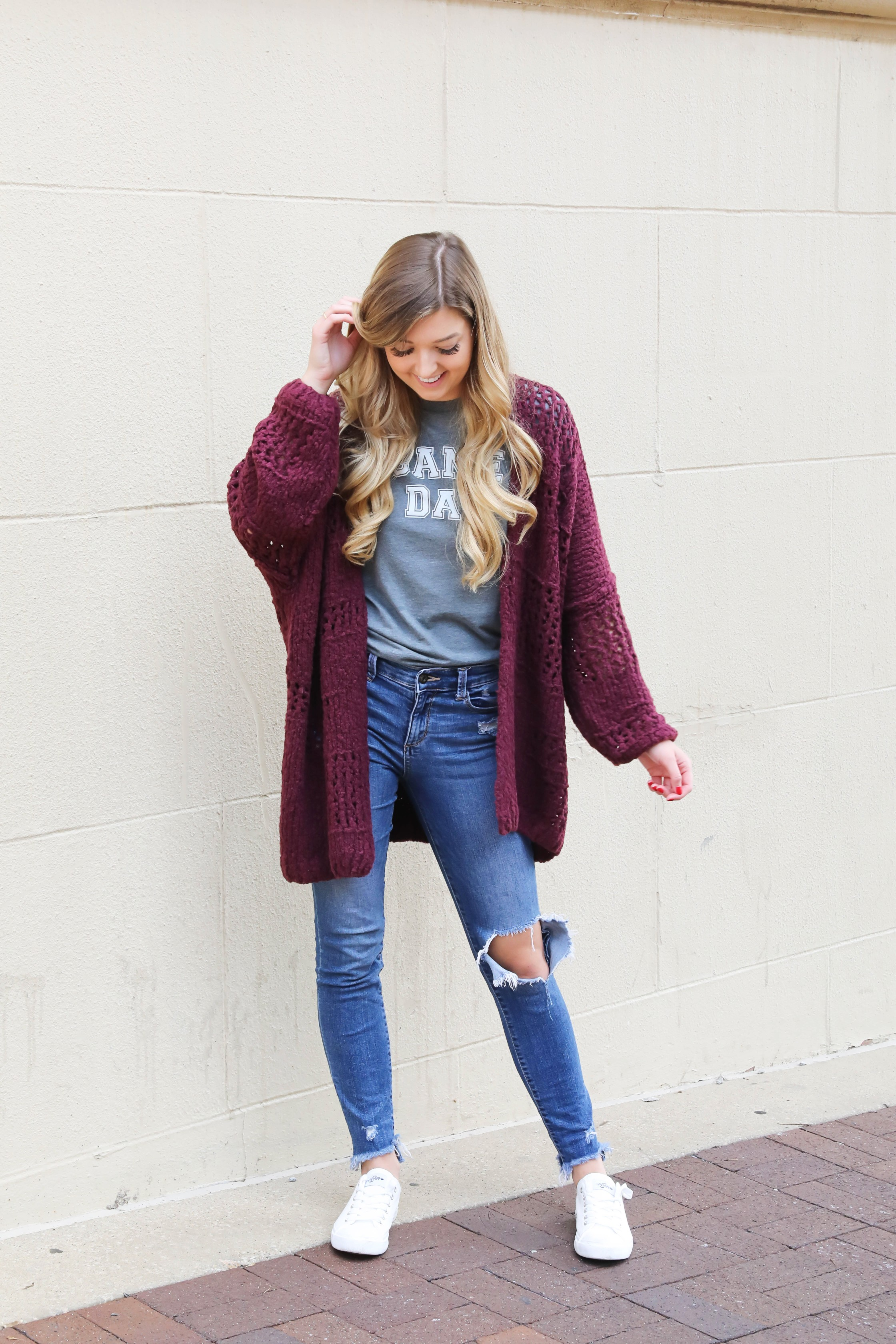 Free People Burgundy cardigan paired with a cute gray game day tshirt! These ripped denim jeans are so perfect for fall and I love these inexpensive white sneakers with the look! This is a perfect game day outfit for football games this fall! Details on daily dose of charm by lauren lindmark