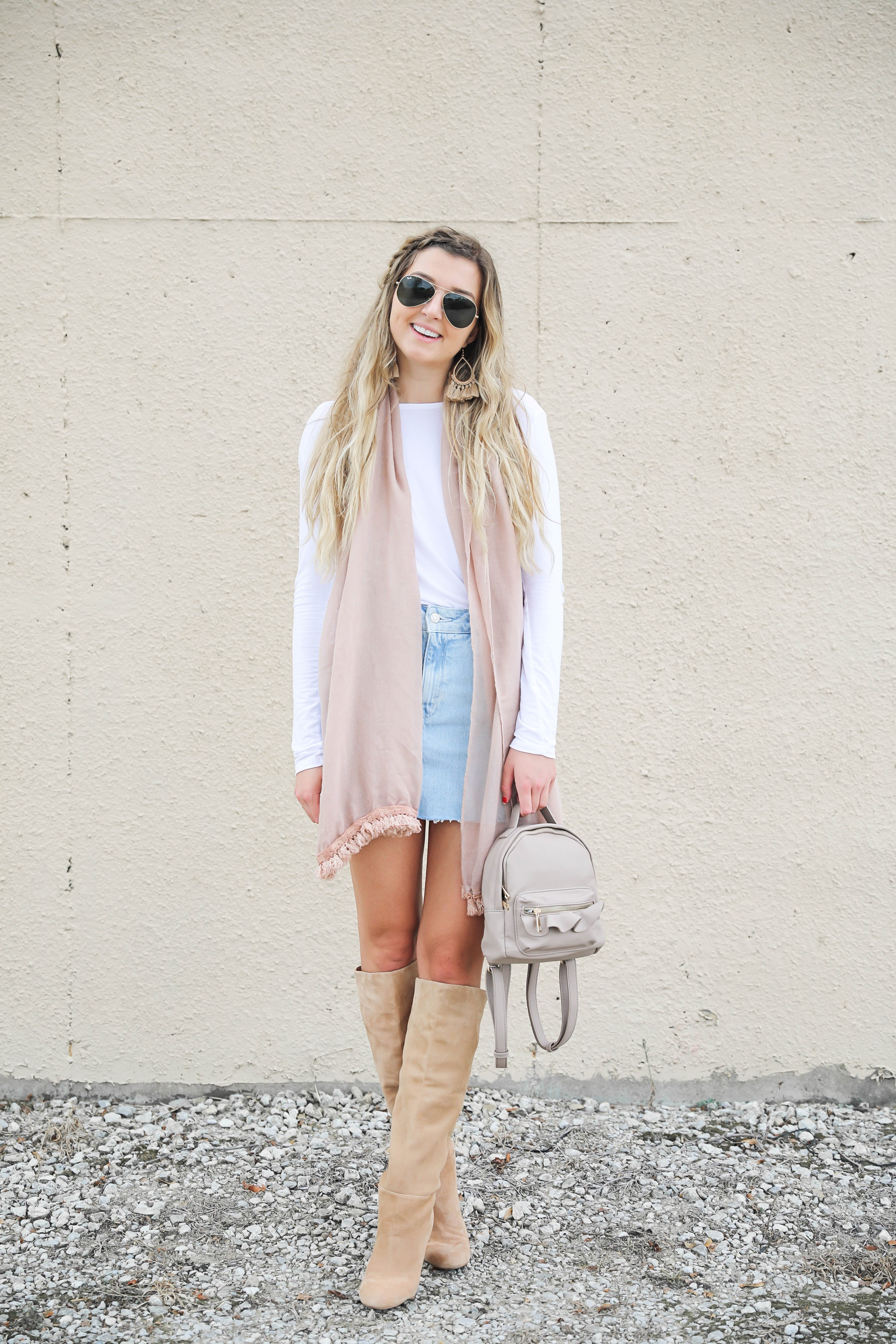 Light denim skirt with a long sleeve white t-shirt! The white t-shirt is open back and only $15! I am obsessed with this pink fringe scarf and these tan booties that totally complete the fall outfit! Details on daily dose of charm by lauren lindmark