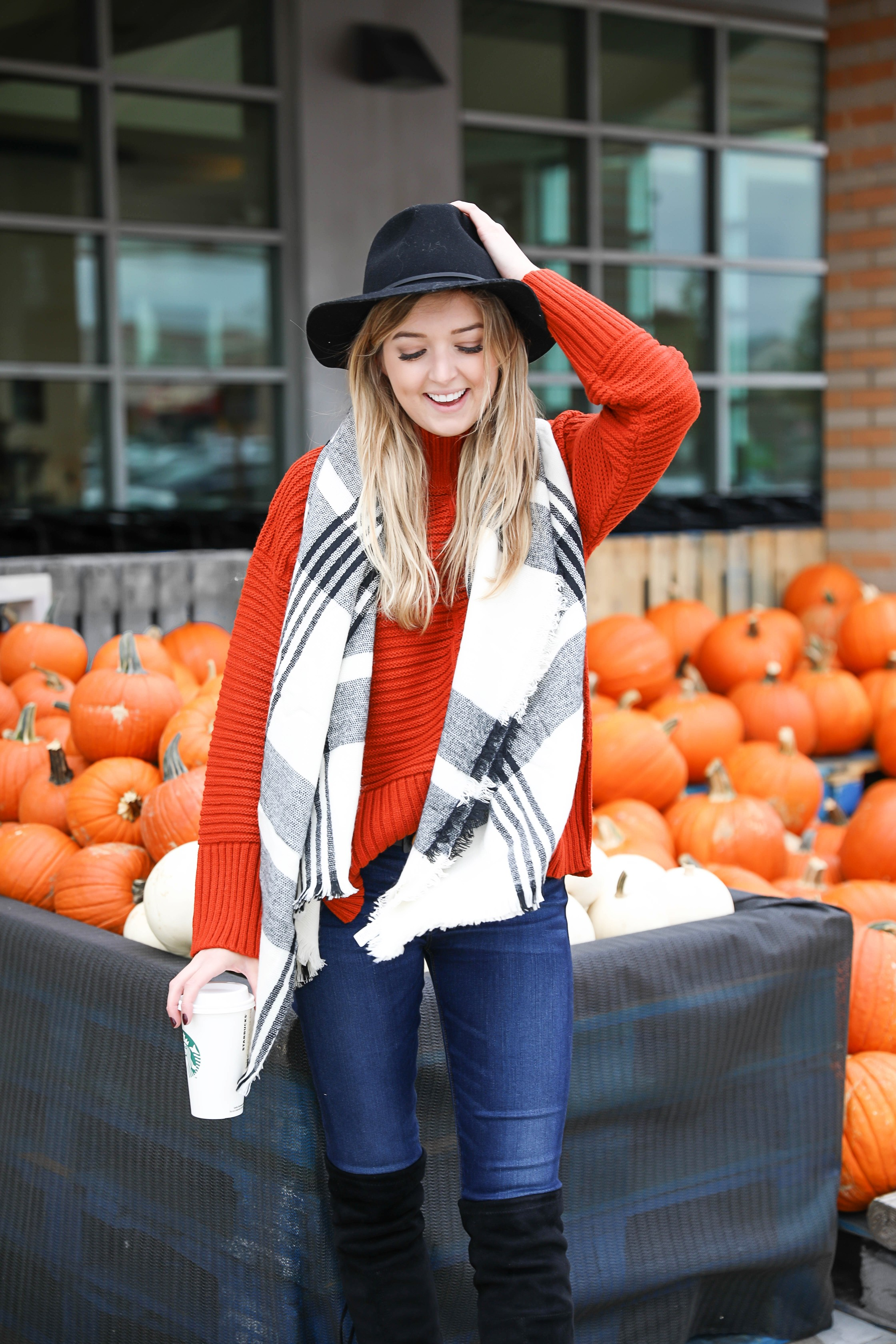 Orange Topshop sweater with a cute black and white scarf that doubles as a poncho! I paired this fall look with these $40 over the knee boots and my favorite black felt hat! Cutest fall outfit ideas on fashion blog daily dose of charm by lauren lindmark