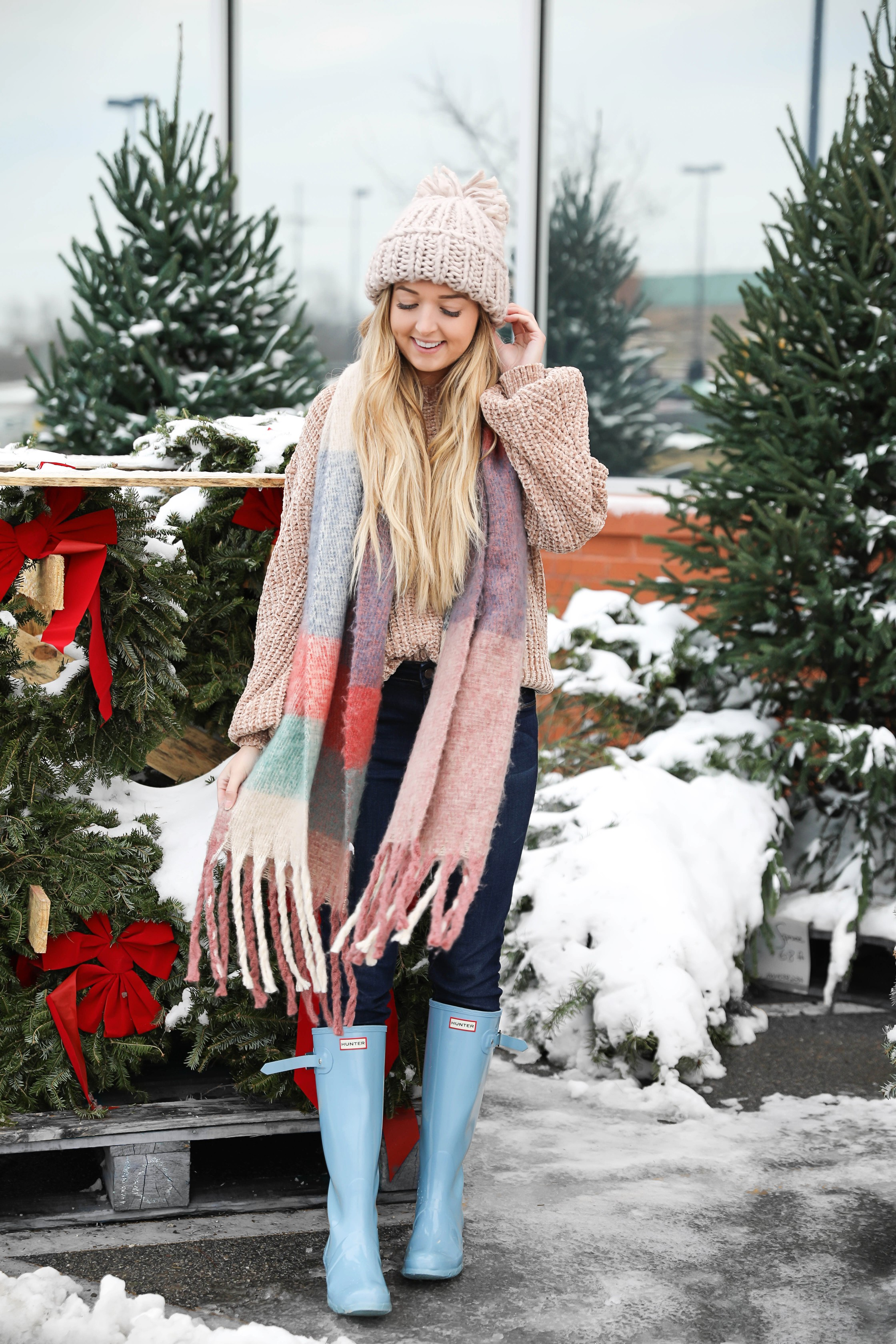 The cutest winter look! I am wearing this super cozy knit beanie, chenille sweater, blue hunter boots, and plaid heavy scarf! I love winter outfits! Photoshoot at a christmas wreath store! Holiday outfit idea on fashion blog daily dose of charm by lauren lindmark