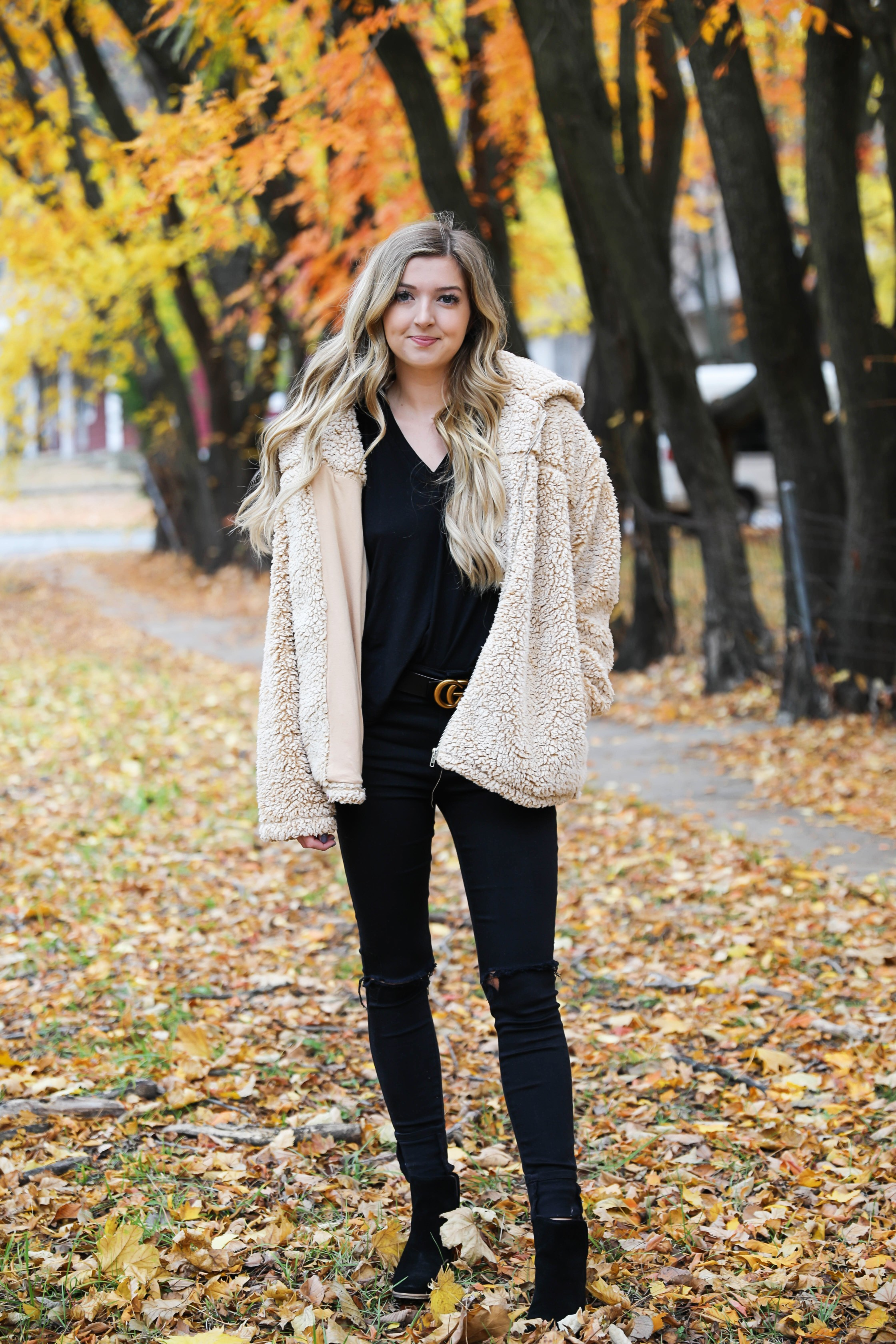 Teddy bear coat roundup! All the comfiest teddy bear fuzzy coats are linked on my blog! I paired mine with an all black outfit and my gucci belt! These are the prettiest photos taken in the fall leaves. Autumn trees are the best! Details on fashion blog daily dose of charm by lauren lindmark