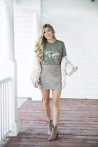 Thanksgiving outfit idea! Thanksgiving look, I love this t-shirt that says thankful for wine! The olive color shirt is so cute for this time of year and looks so good with the suede skirt and pom cardigan! Details on fashion blog daily dose of charm by lauren lindmark