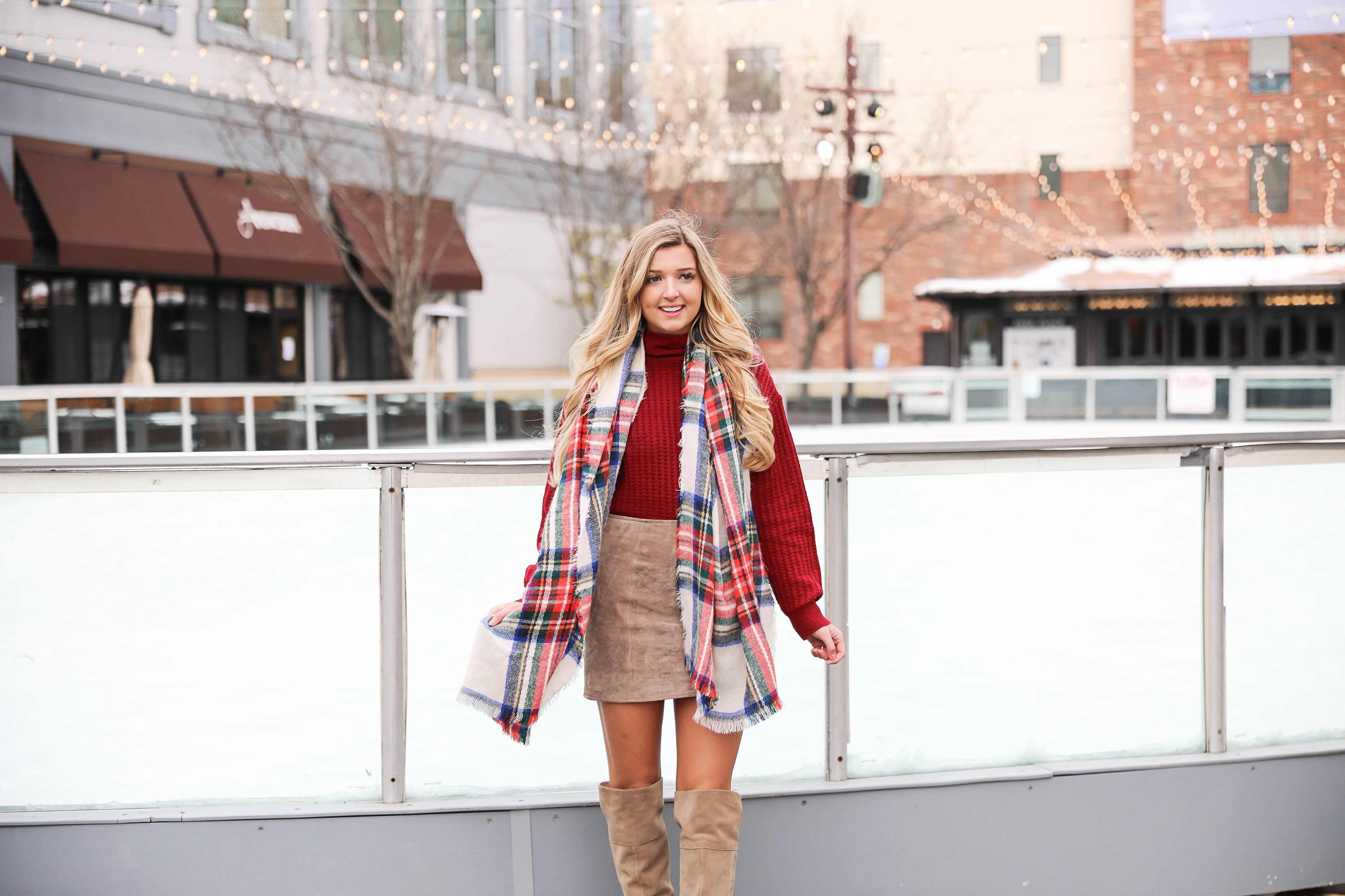 Red turtleneck sweater paired with my favorite suede skirt and Vince Camuto over the knee boots! This holiday look looks so cute with this red and green plaid scarf! The cutest winter outfit on the fashion blog daily dose of charm by lauren lindmark