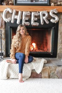 """Happy New Year! The cutest photoshoot with """"cheers"""" balloons! New Year's Eve photoshoot next to a cozy fireplace! I also list out all my resolutions for the year! My cute Pomeranian pup is featured in some of the photos! Details on fashion blog daily dose of charm by lauren lindmark"""